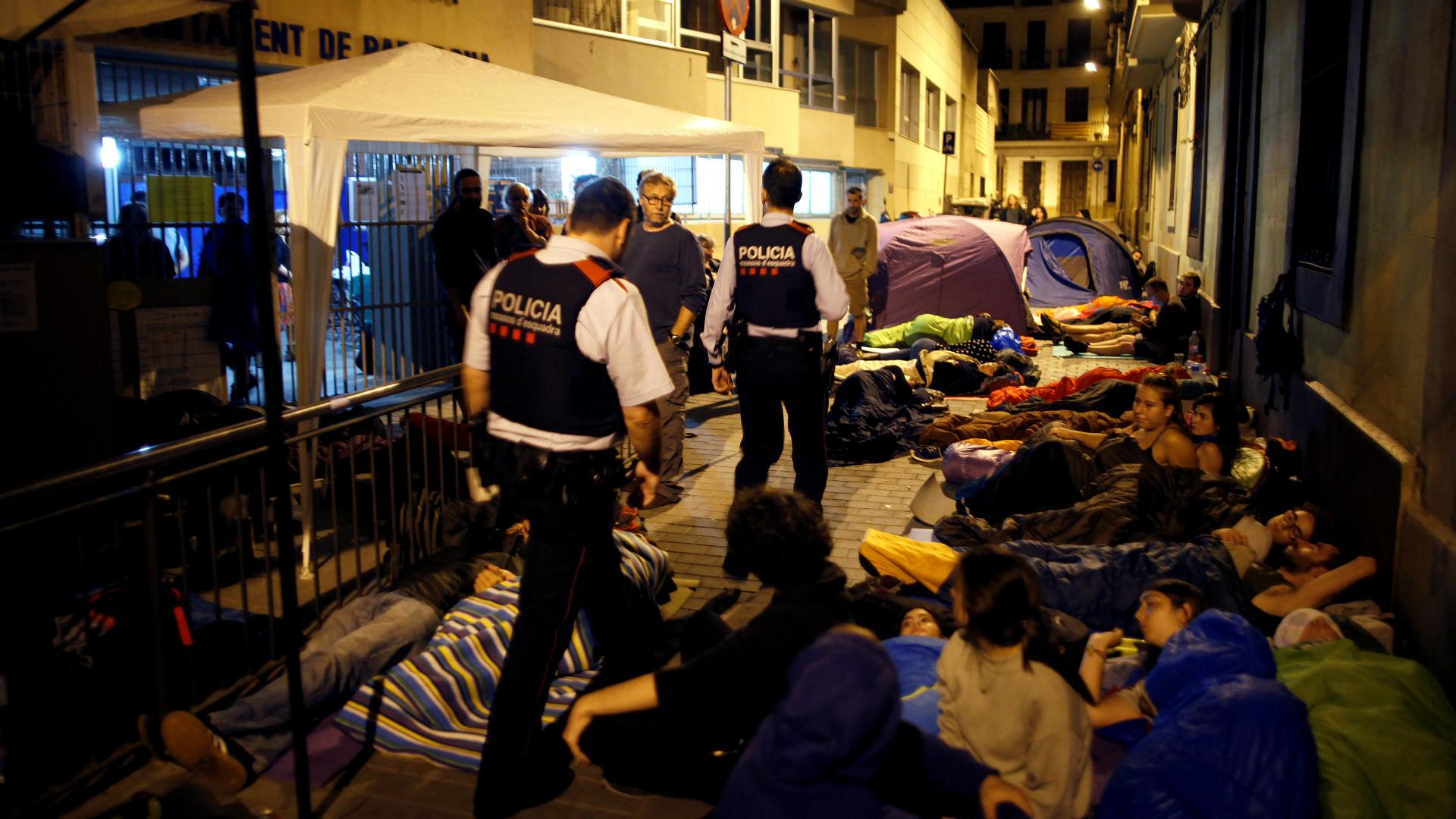 La policía catalana inspecciona una colegio donde la gente acampa. (Reuters)