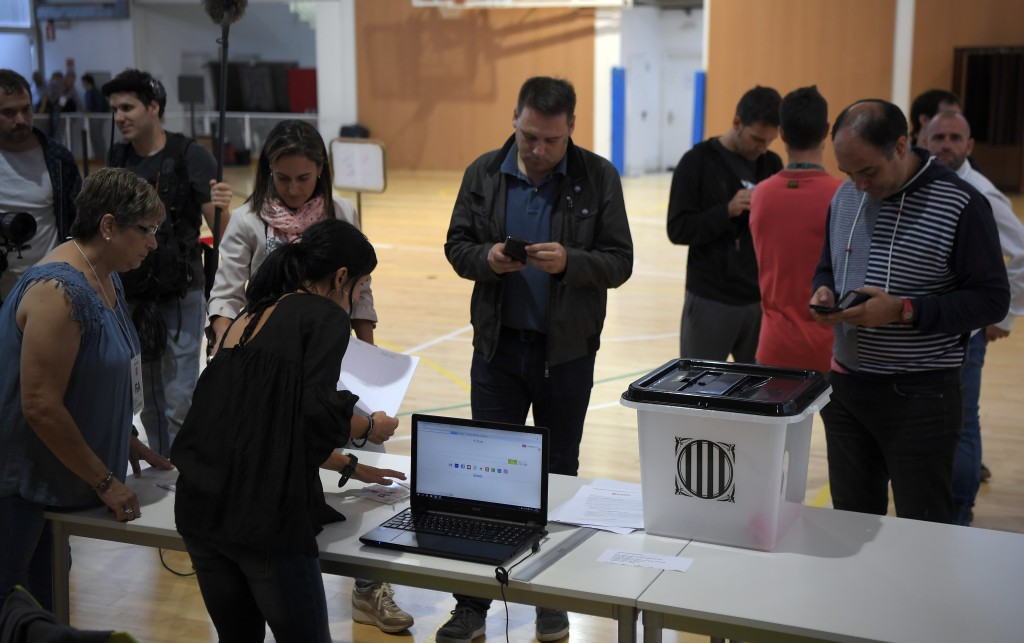 People set up a polling station in Sarria de Ter, where Catalan president will vote, on October 1, 2017, on the day of a referendum on independence for Catalonia banned by Madrid. More than 5.3 million Catalans are called today to vote in a referendum on independence, surrounded by uncertainty over the intention of Spanish institutions to prevent this plebiscite banned by justice. / AFP PHOTO / LLUIS GENE /