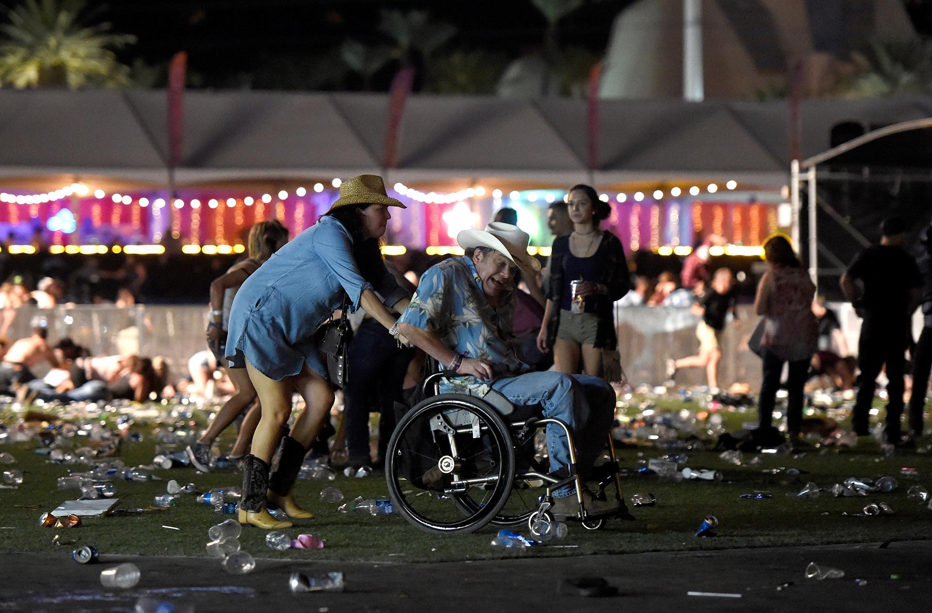 Un hombre en silla de ruedas es ayudado a escapar después de los disparos