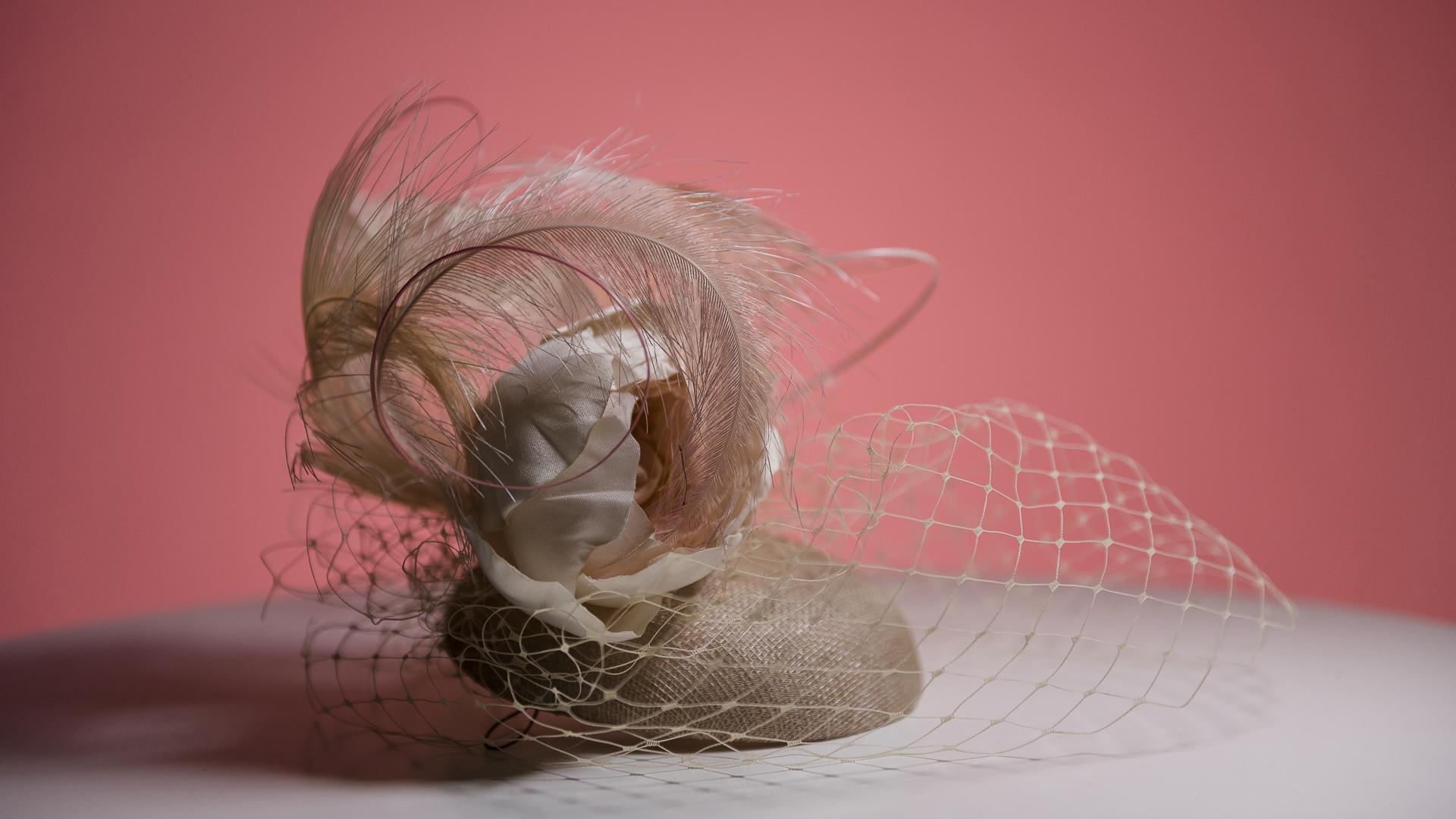 La sombrera Laura Noetinger diseñó el casquete con voilette, plumas y rosa