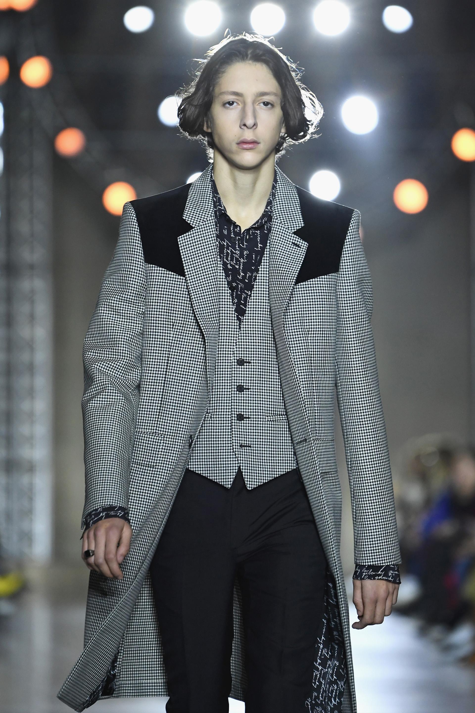 Look formal, un traje de tres piezas. Sobretodo cuadrillé en gris blanco y hombros en negro con chaleco en el mismo print combinando con camisa estampada y pantalones chupín negro