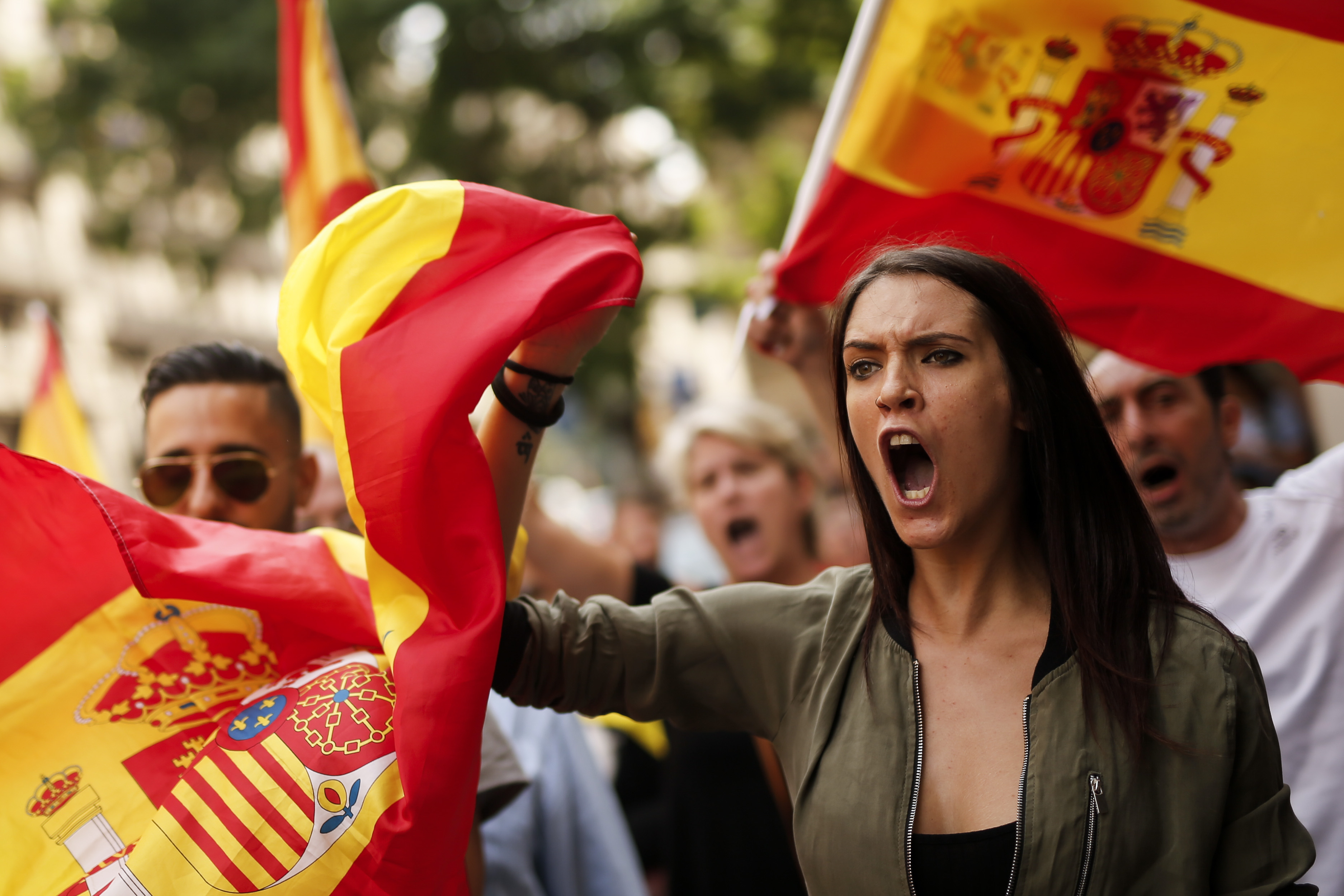 Protestors hold Spanish flags during a demonstration against independence in Catalonia called by the xenophobic far-right party 'Platform for Catalonia' (PXC) in front of the Spanish National Police headquarters in Barcelona, on September 30, 2017. Hundreds of people, many waving red and yellow Spanish flags, rallied in Barcelona in favour of Spanish unity today, a day before a banned independence referendum in Catalonia. / AFP PHOTO / PAU BARRENA /