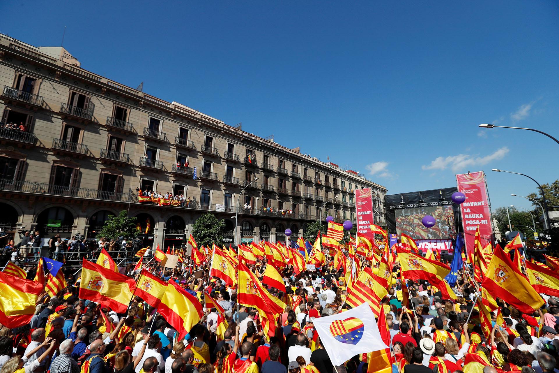 """Muchos en la multitud llevaban banderas de España y Cataluña y corearon lemas como """"No se engañen, Cataluña es España"""" y """"Puigdemont a prisión"""" refiriéndose al presidente de la región"""