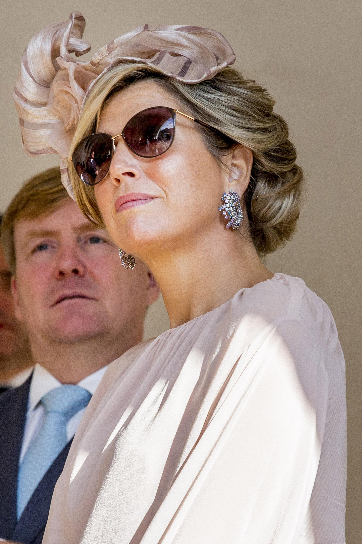 La monarca se protegió del sol con unos anteojos marrones y con metal dorado. Unos pendientes aportaron aún más glamour a su elegante estilo