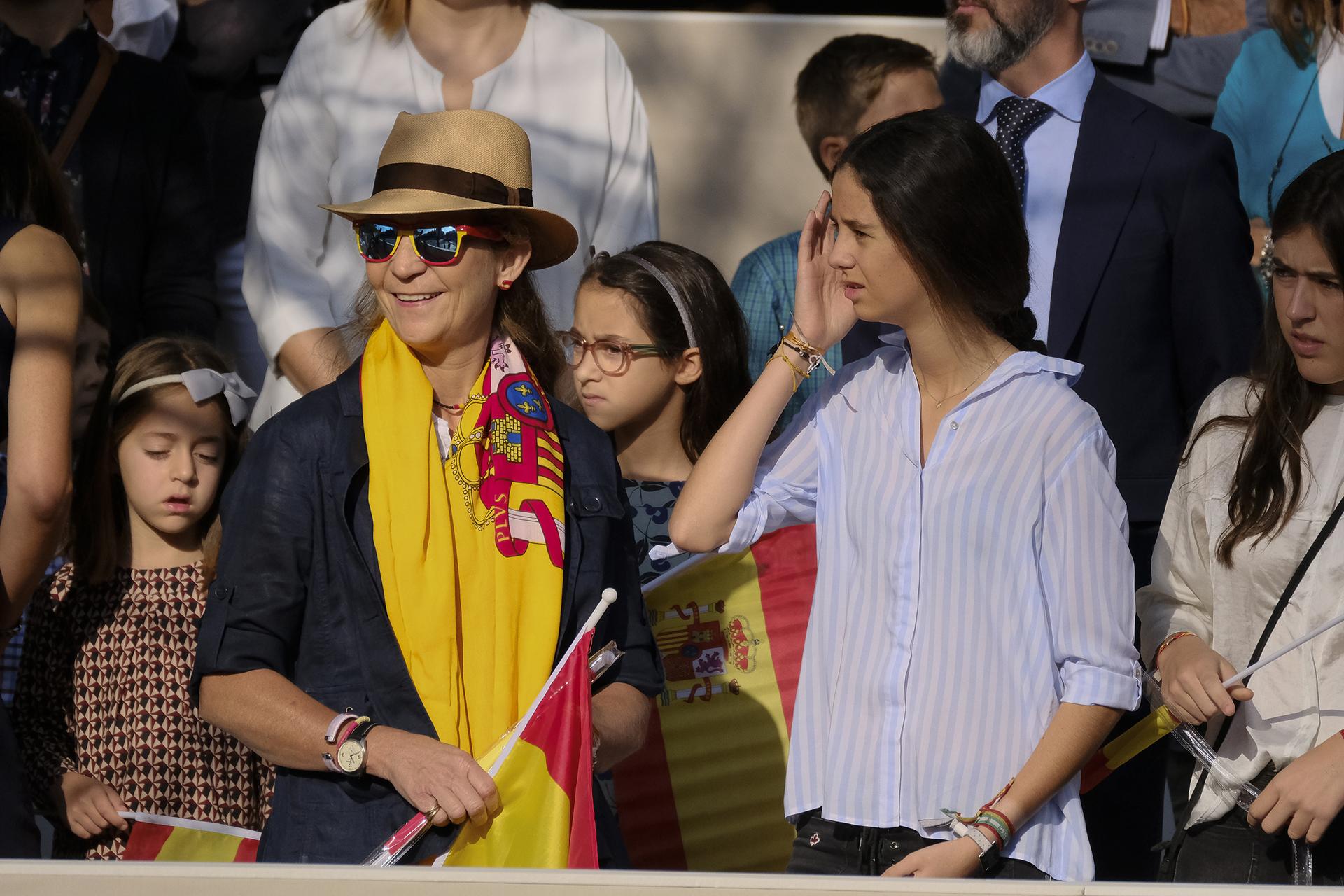 Con un estilo más informal, luciendo un sombrero, una bandera como chalina y otra en su mano, la Infanta Elena festejó junto a su hija Victoria Federica de Marichalar y Borbón