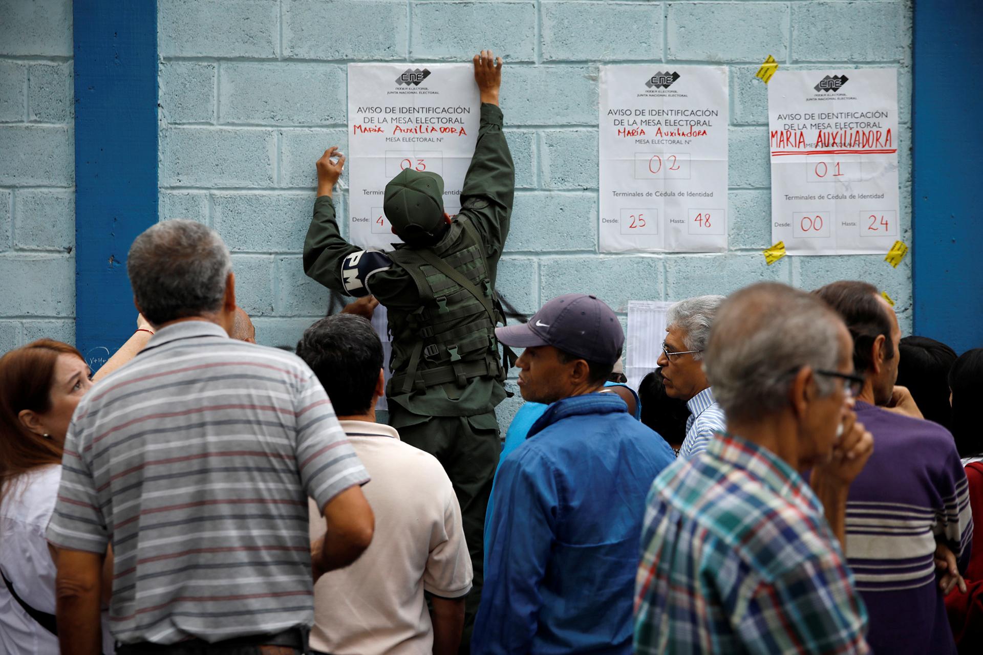 Un uniformado coloca las guías en un centro de votación
