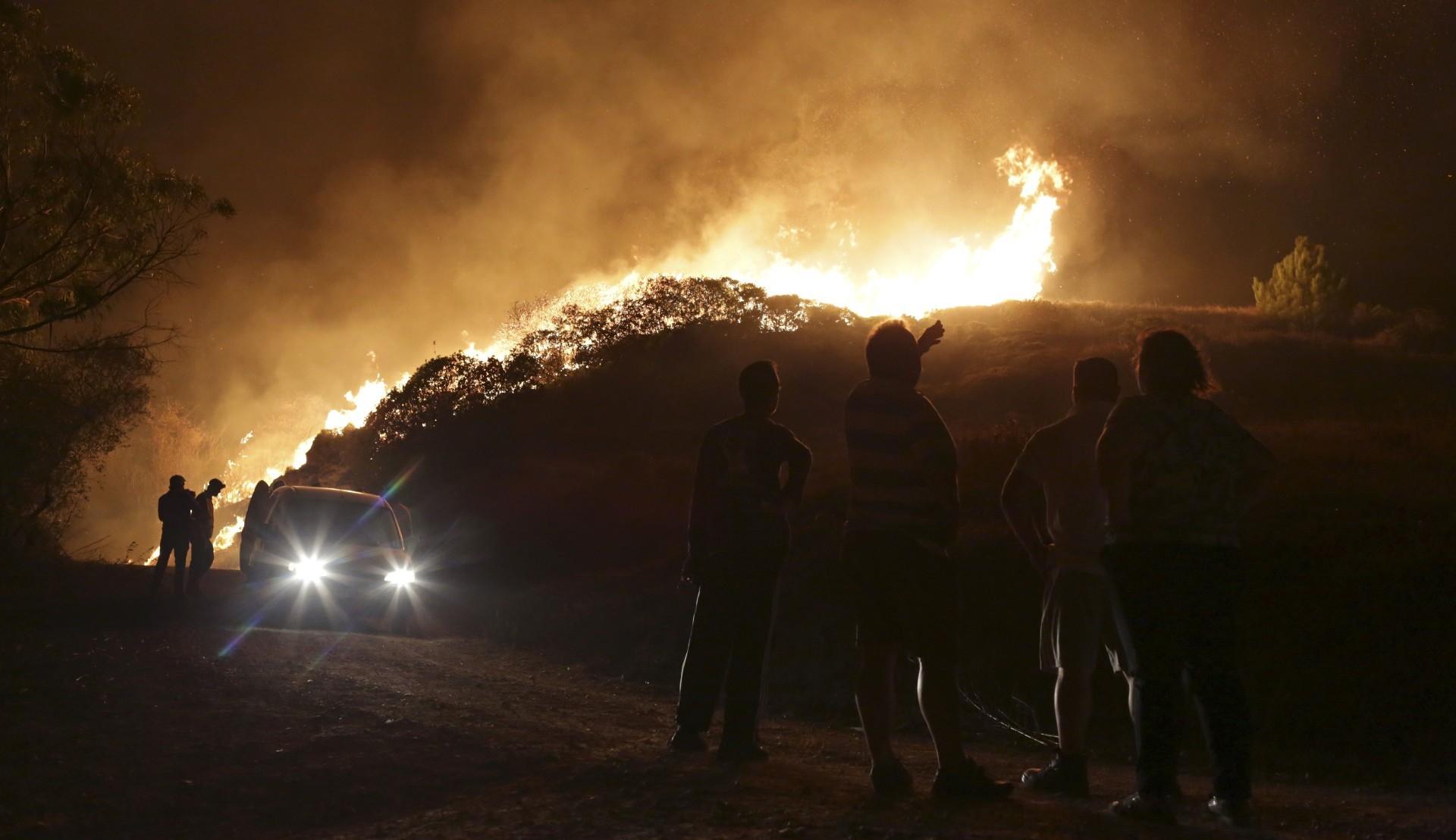 La gente observa las llamas en las afueras de Obidos (AP Photo/Armando Franca)