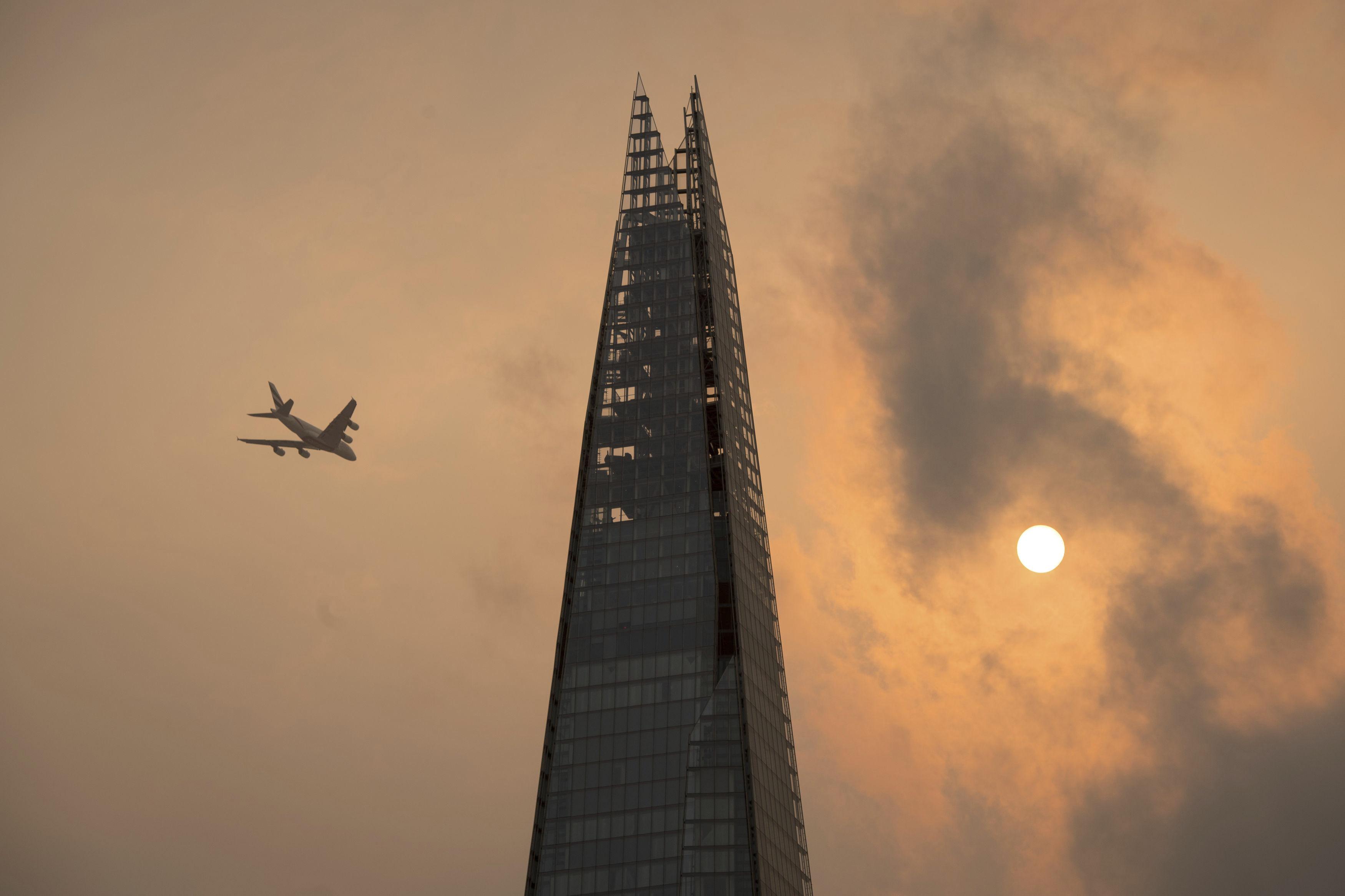 Un avión vuela sobre el rascacielos The Shard en el centro de Londres (Dominic Lipinski/PA vía AP)