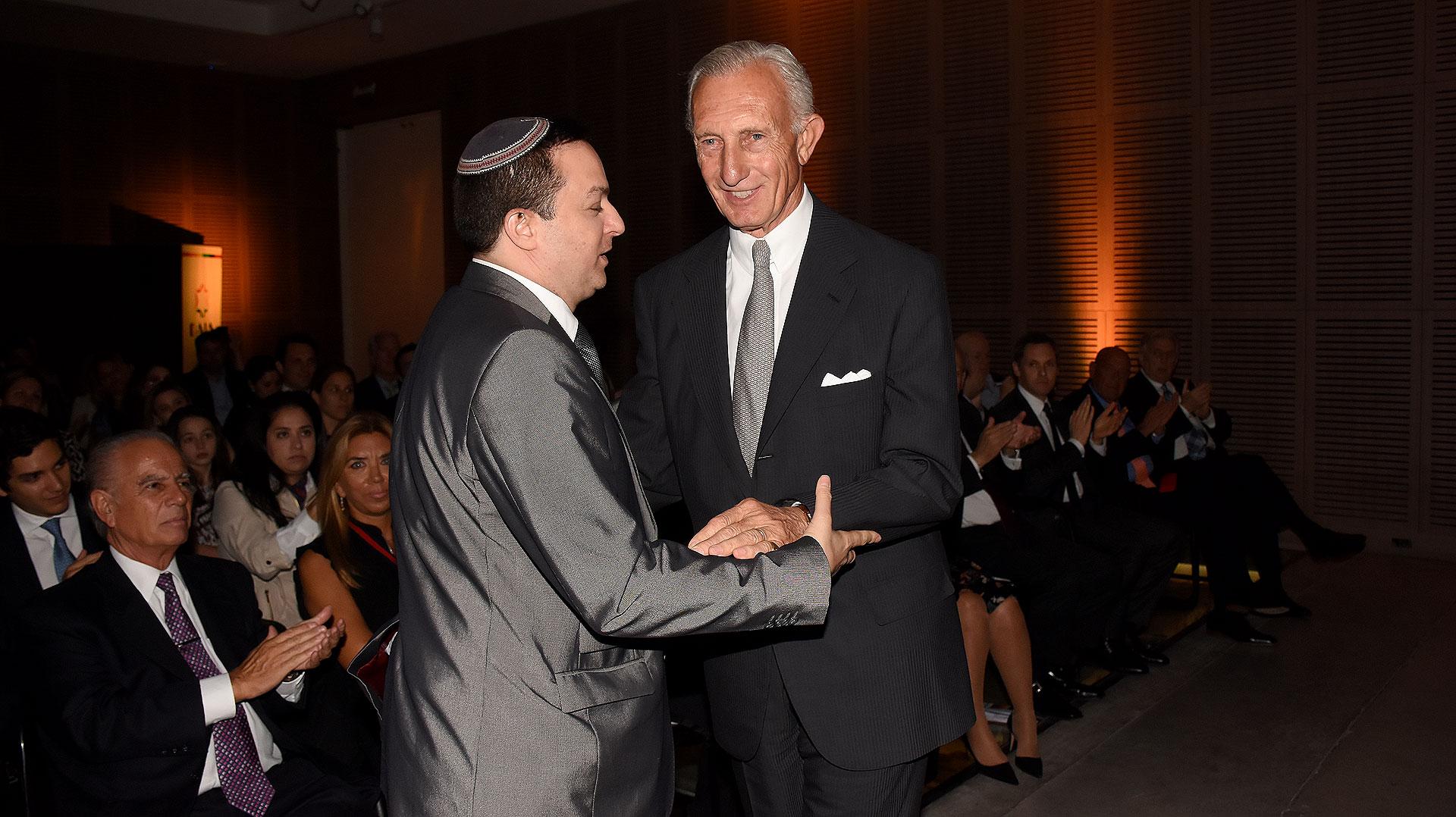 El presidente de la DAIA, Ariel Cohen Sabban, le entrega el premio al empresario Jorge Neuss