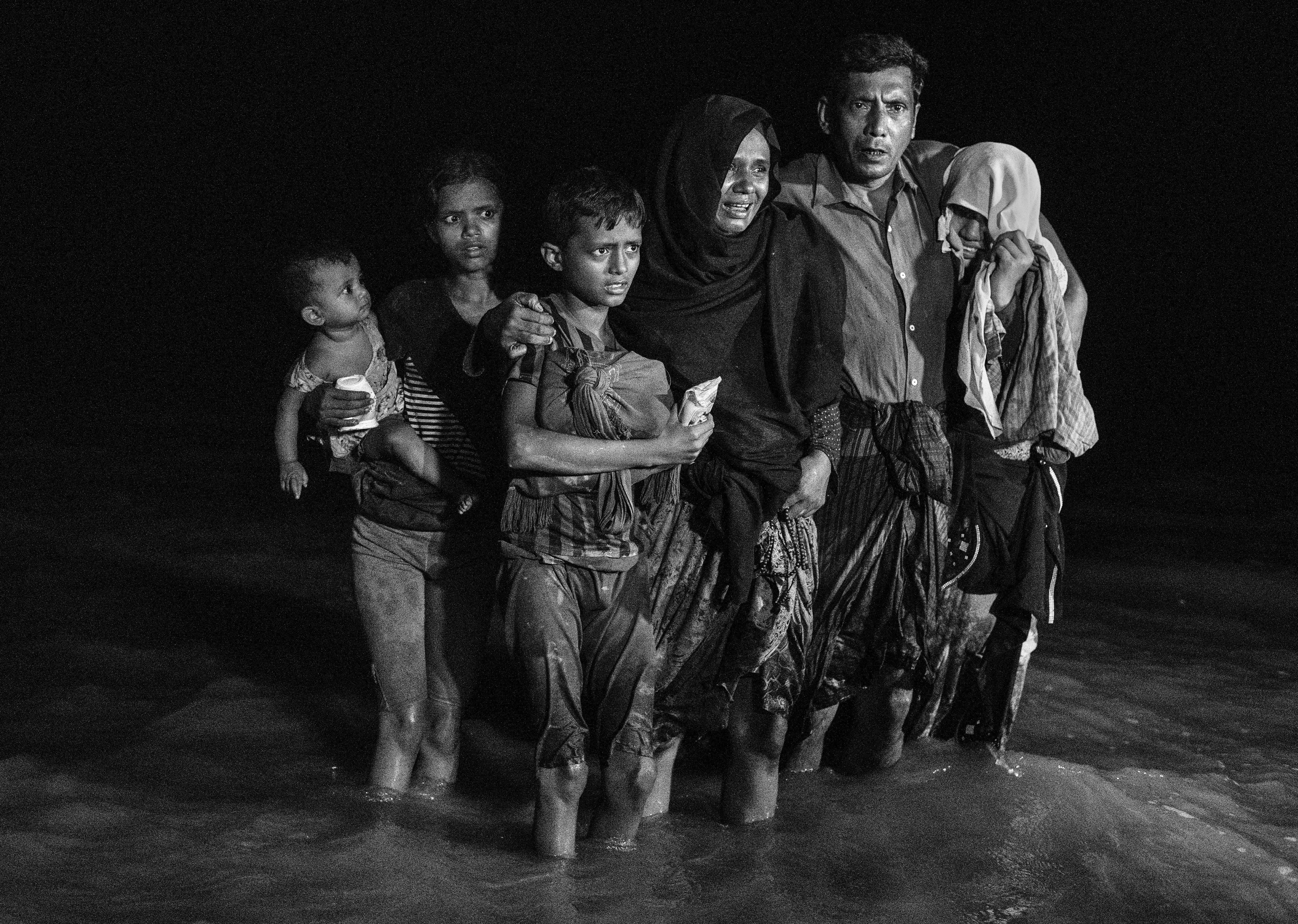 Una familia tras desembarcar en la orilla bangladesí del río Naf (Kevin Frayer/Getty Images)