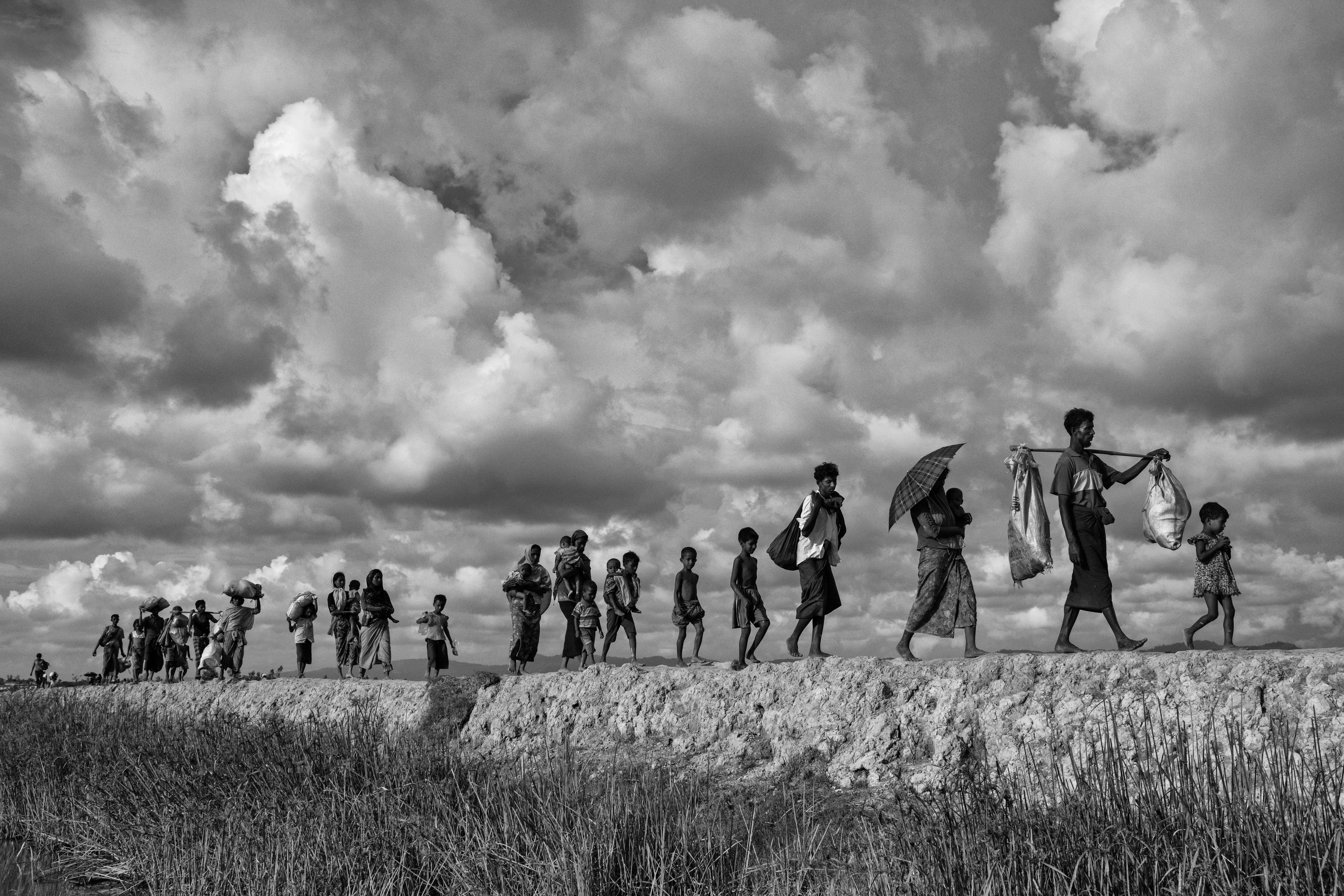 Refugiados rohinyás cargan sus pertenencias mientras cruzan la frontera entre Myanmar y Bangladesh (Kevin Frayer/Getty Images)