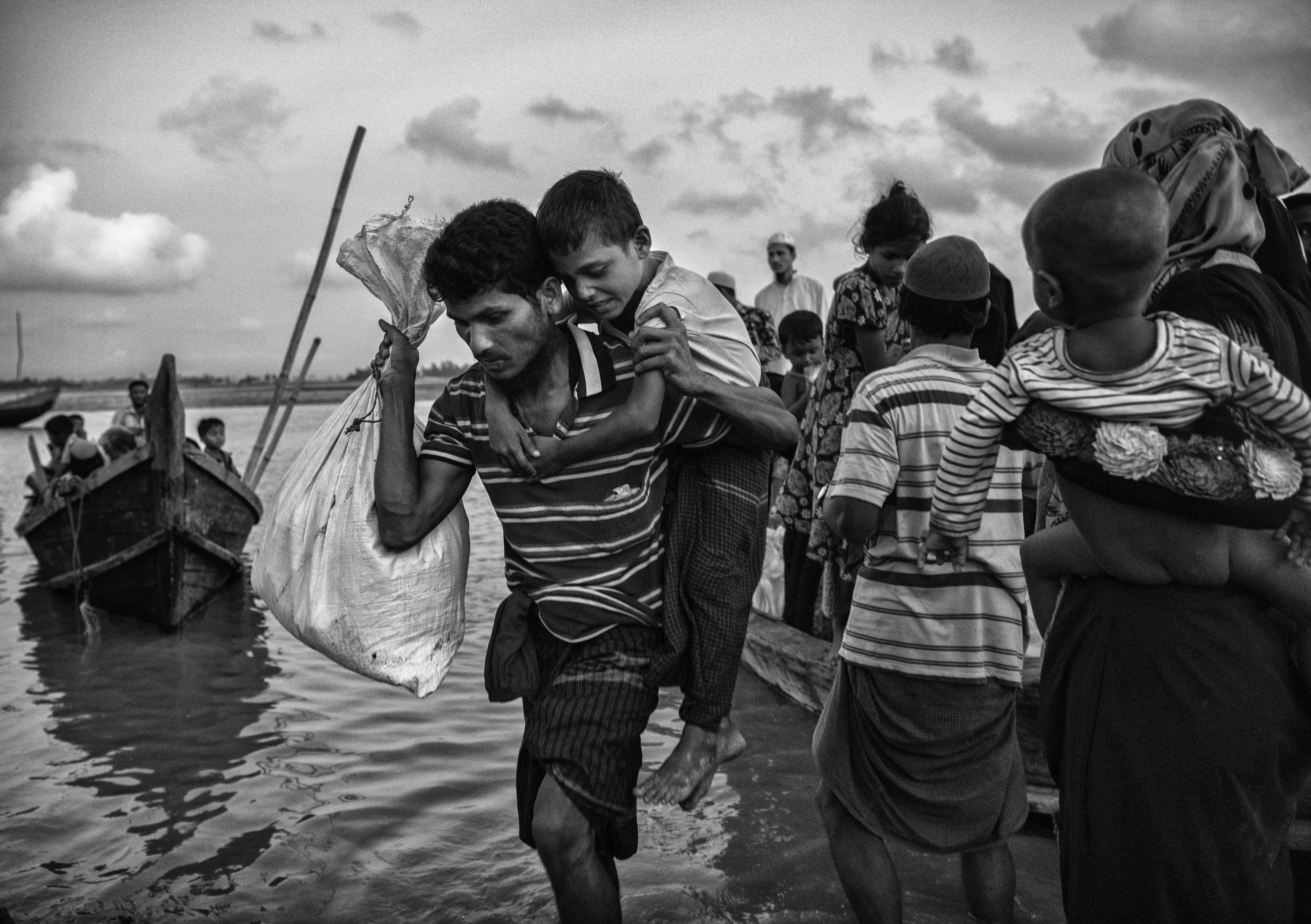 Un hombre y un niño al llegar a la playa del río Naf, en Shah Porir Dwip (Kevin Frayer/Getty Images)