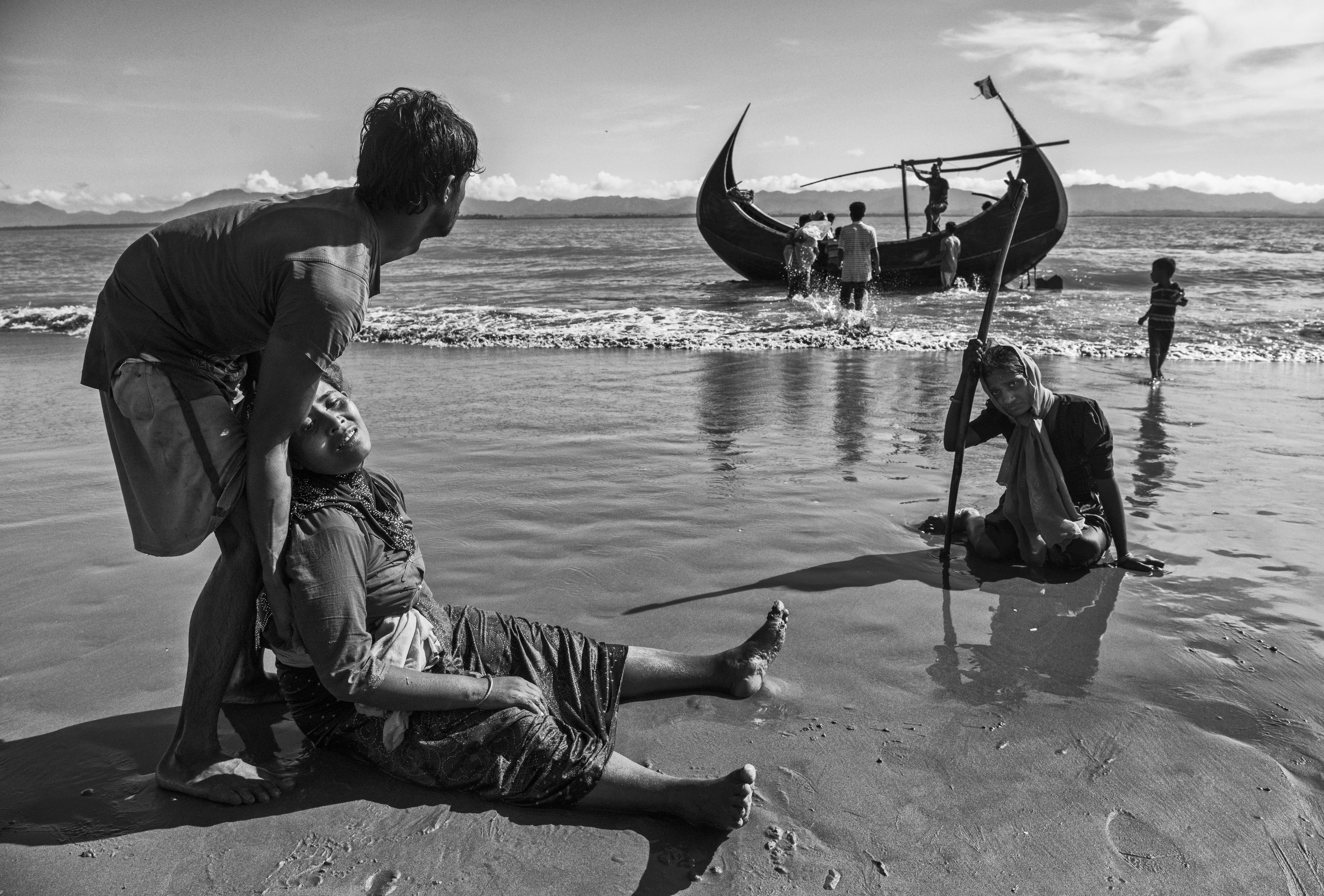 Una mujer descansa agotada en la playa del río Naf, en Shah Porir Dwip, tras escapar de su aldea en Myanmar (Kevin Frayer/Getty Images)