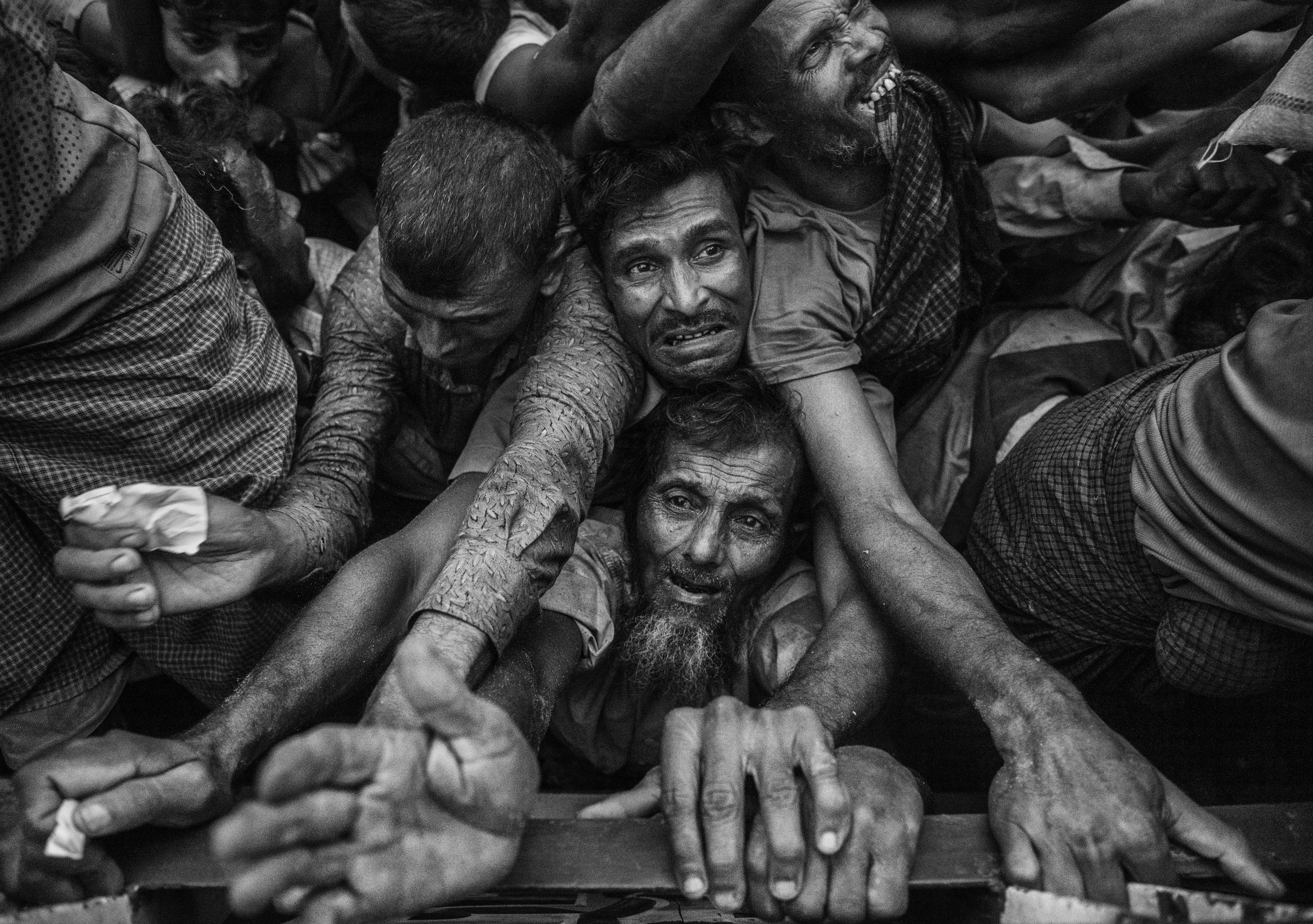 La desesperación de unos hombres durante la distribución de comida en un campo de refugiados (Kevin Frayer/Getty Images)