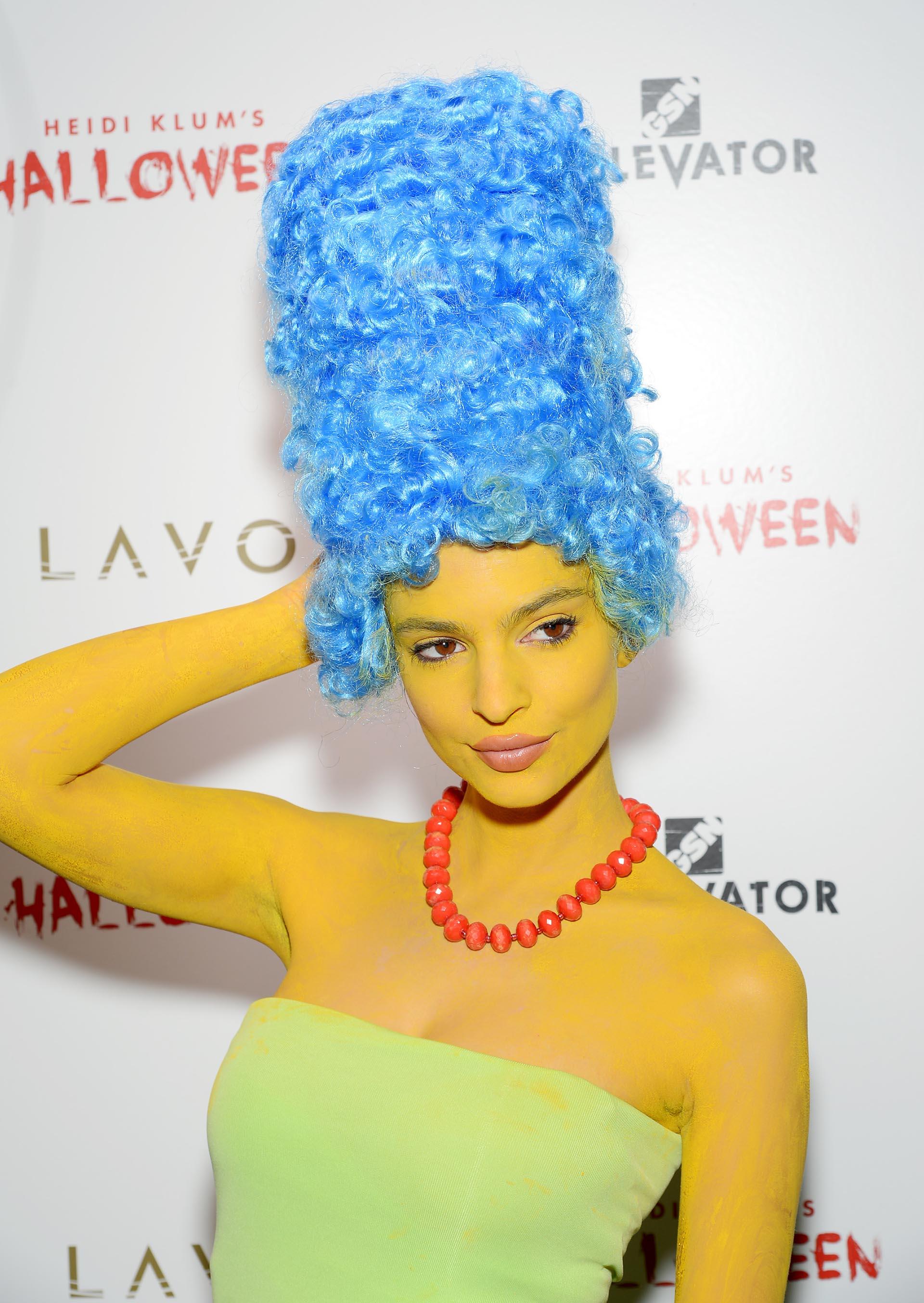 La sexy modelo -Emily Ratajkowski- escogió interpretar a Marge Simpson: pintó su cuerpo de amarillo, lució una peluca extra grande en color azul y su icónico collar