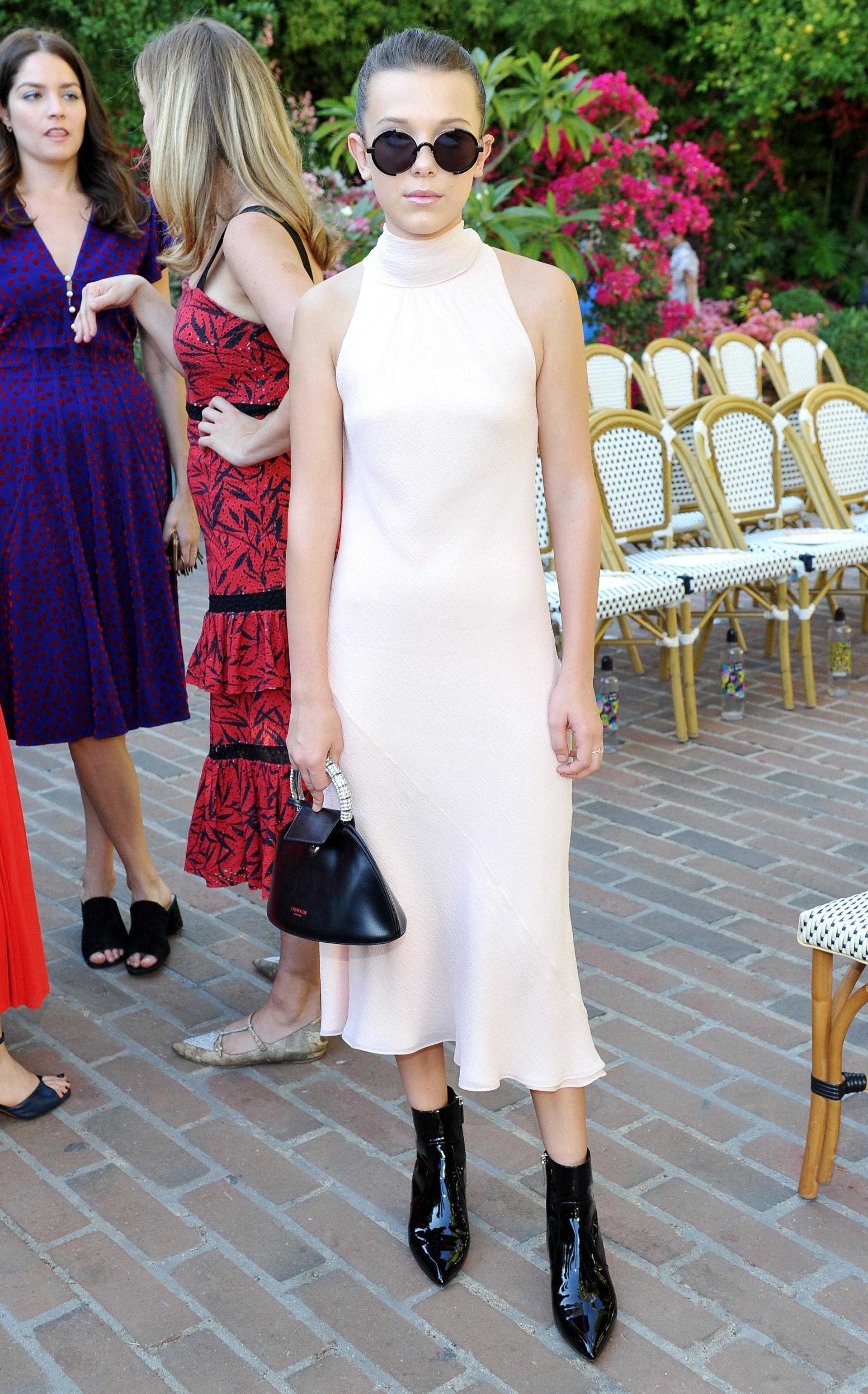 Millie Bobby Brown durante el desfile CFDA para Vogue, con un vestido en rosa empolvado de corte asimétrico de la firma Calvin Klein que rápidamente se convirtió en viral. Su presencia en la primera fila ya es moneda corriente