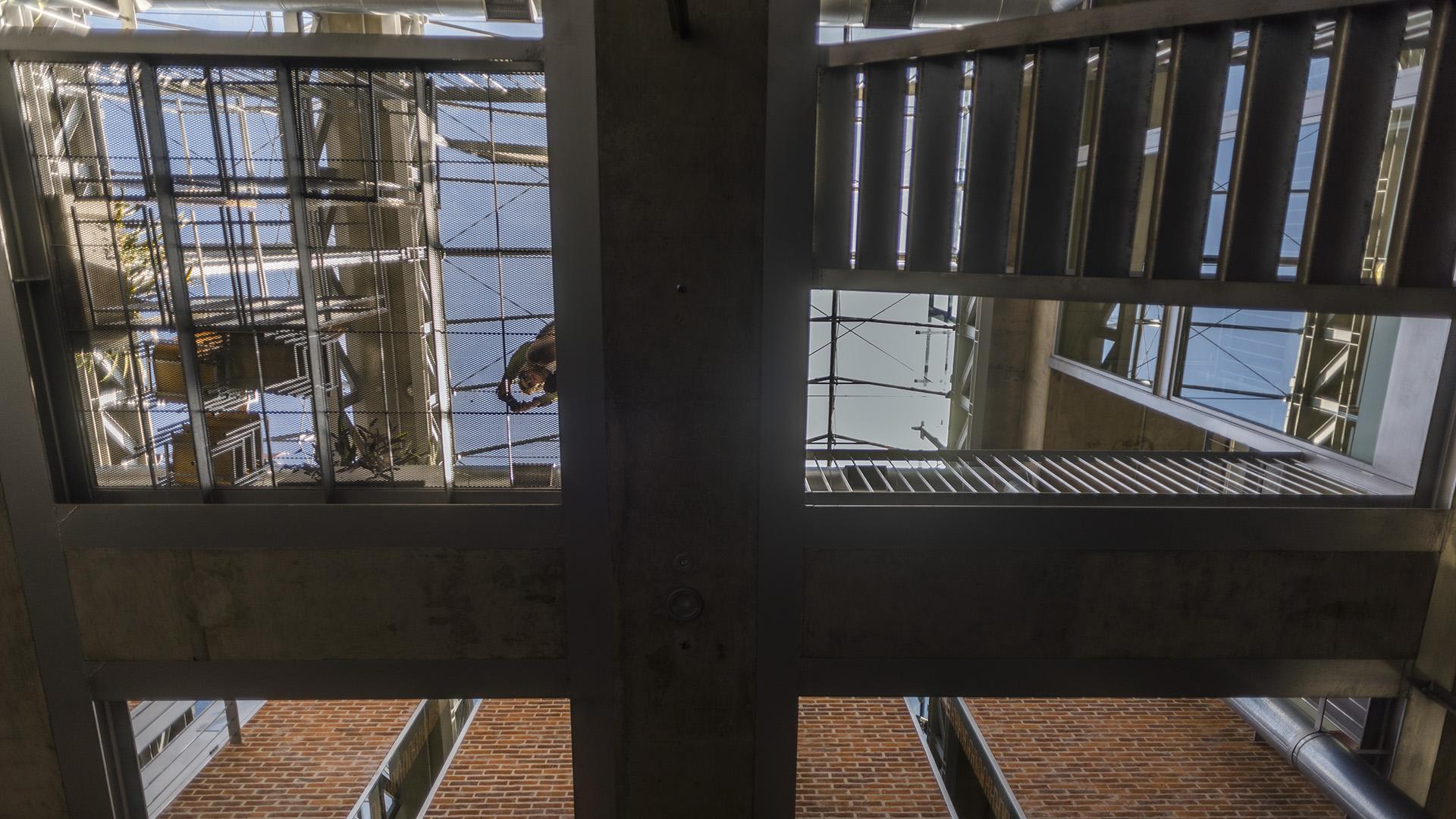 El sistema de planos paralelos, recortados irregularmente, de hierro y hormigón que construye las pasarelas, patios y los entrepisos, define violentamente las vinculaciones horizontales y verticales