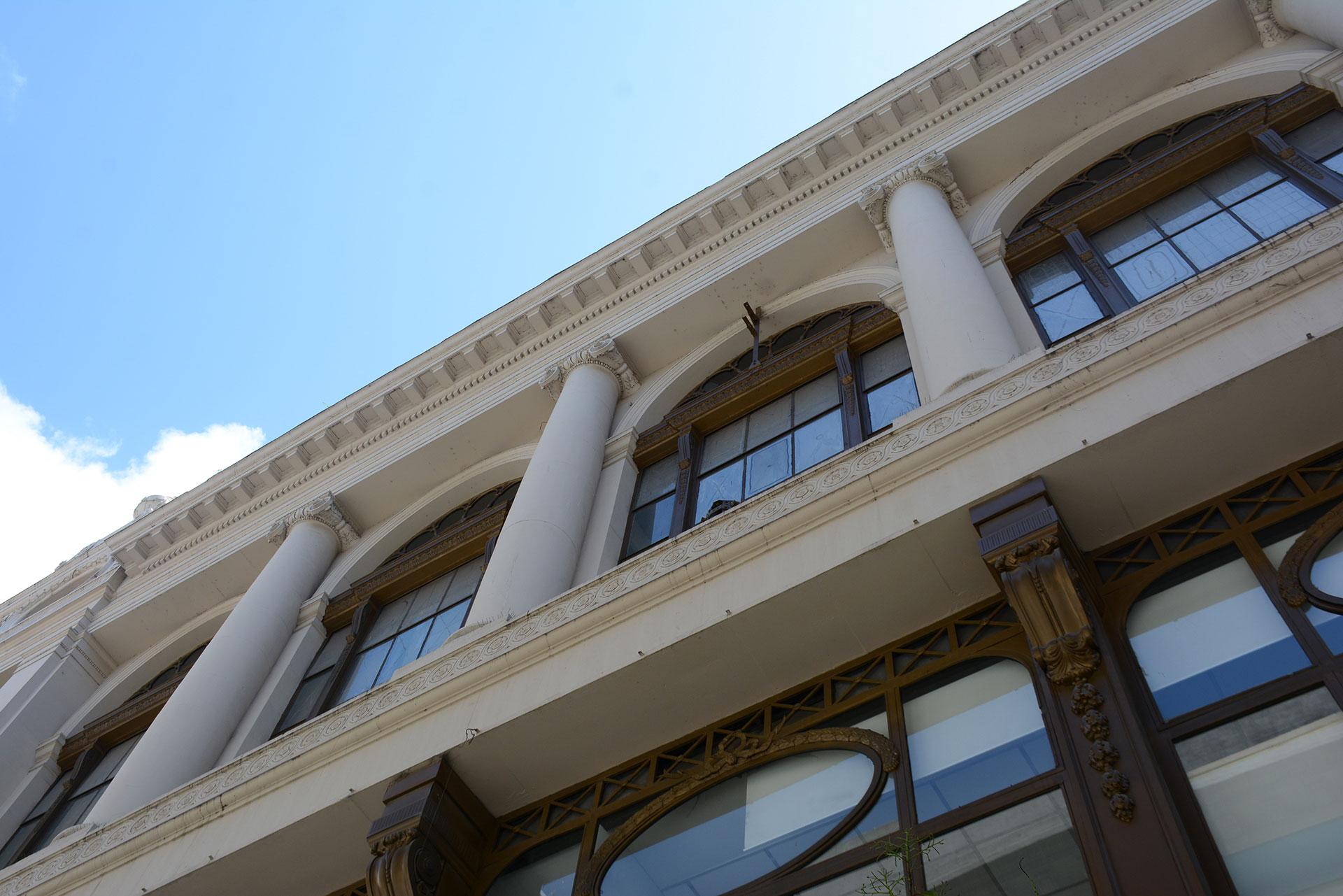 Su fachada es completamente transparente en los niveles inferiores, donde el frente se construye con perfilerías metalicas ornamentadas, grandes paños de vidrio, que solo se interrumpen por columnas de orden dórico en planta baja y primer piso y jónico en el segundo nivel