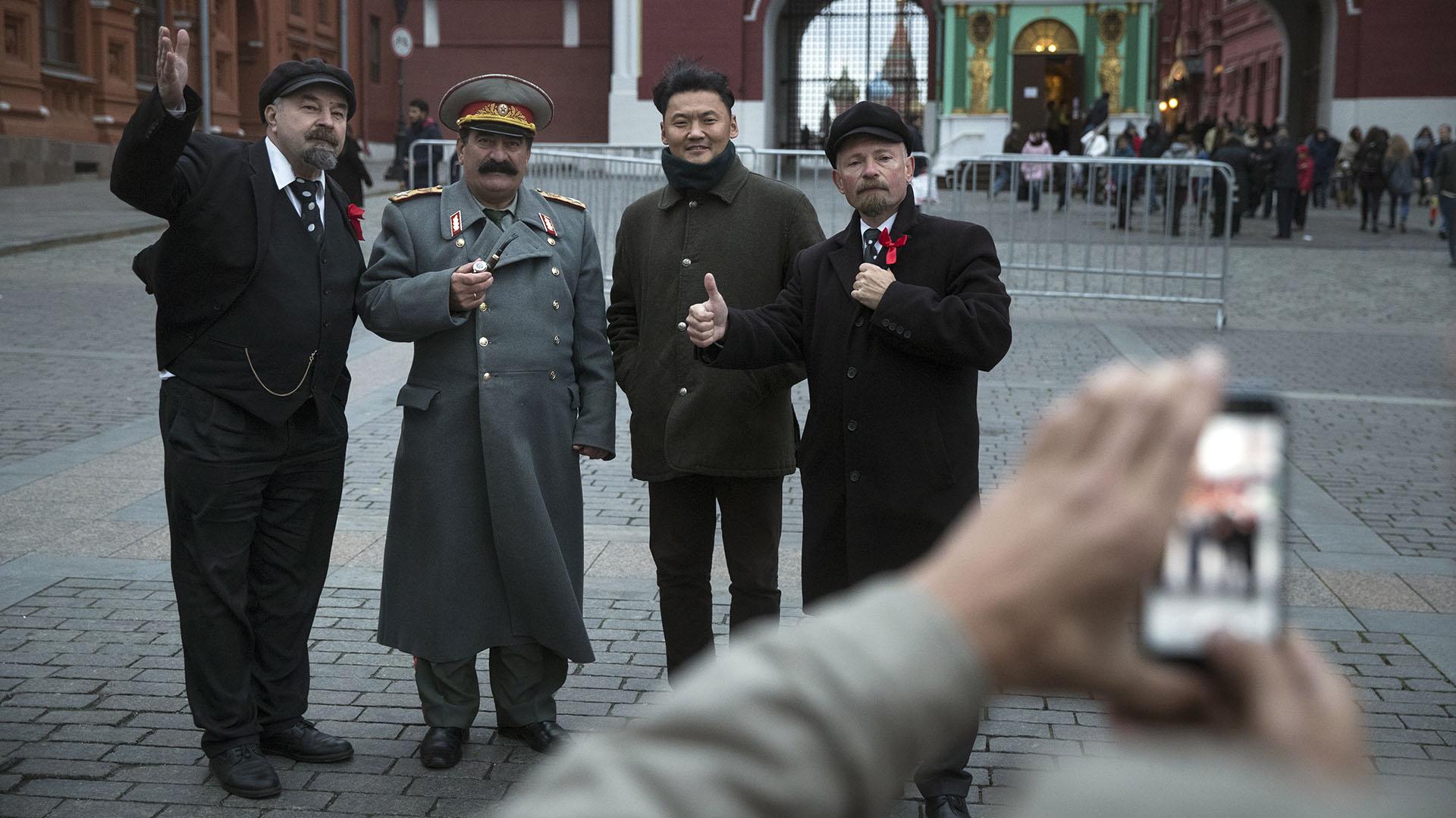 Sergei Soloviev y otros imitadores se fotografían junto a un turista en la plaza roja (AP Photo/Pavel Golovkin)