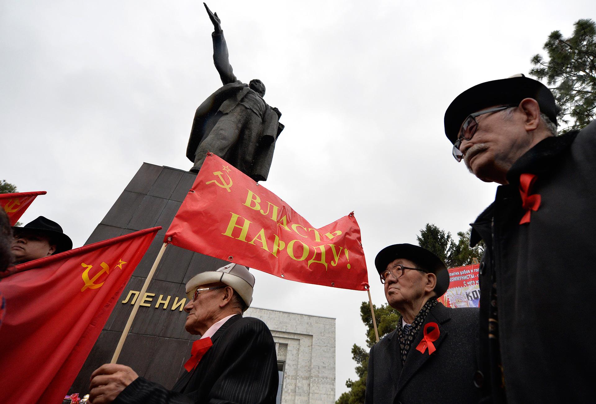 Activistas junto a una estatua de Lenin (AFP)