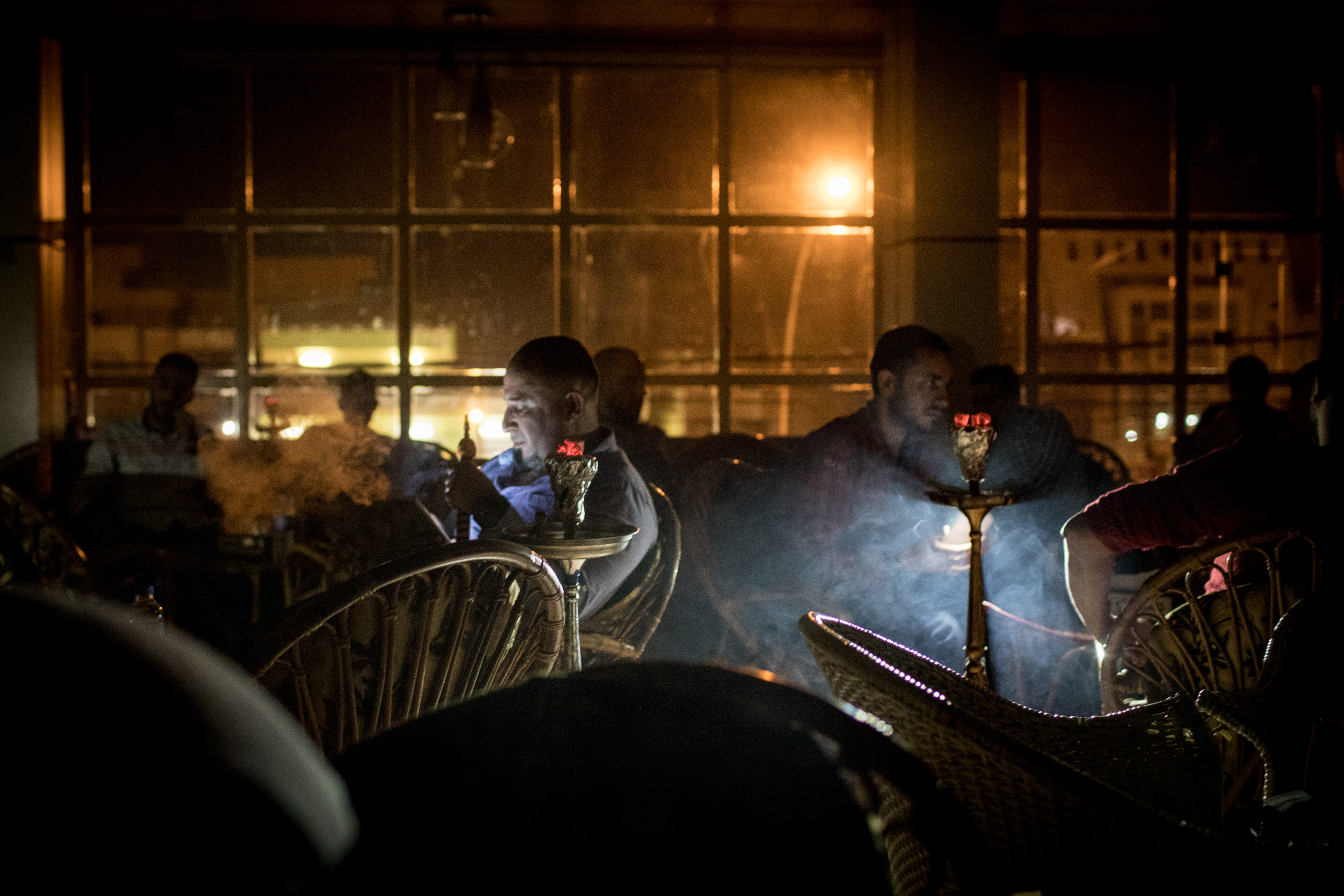 Hombres fuman en un café durante un corte de luz (Chris McGrath/Getty Images)