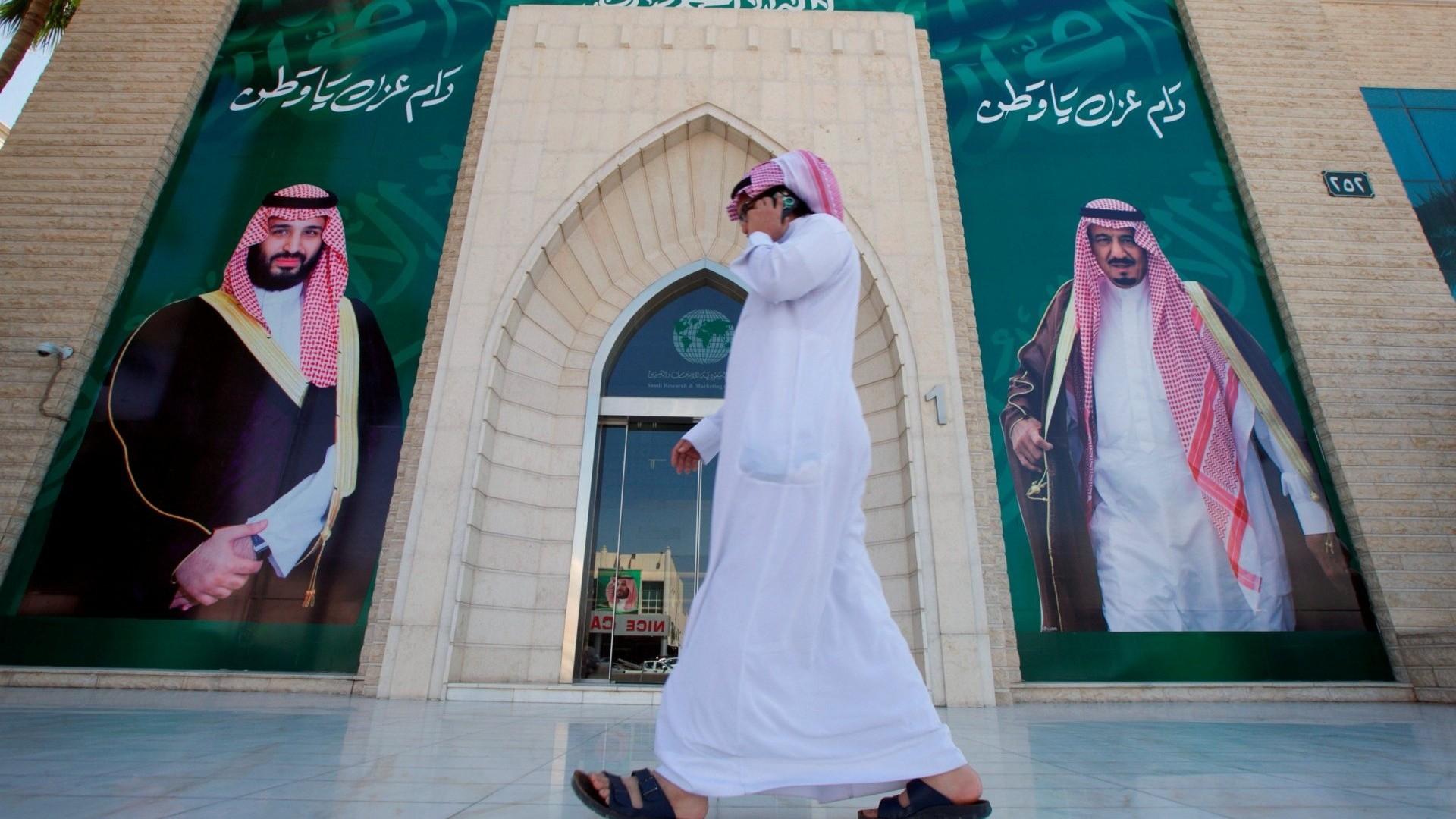 Un hombre camina junto a imágenes del rey Salman y el príncipe Mohammed bin Salman (Reuters)