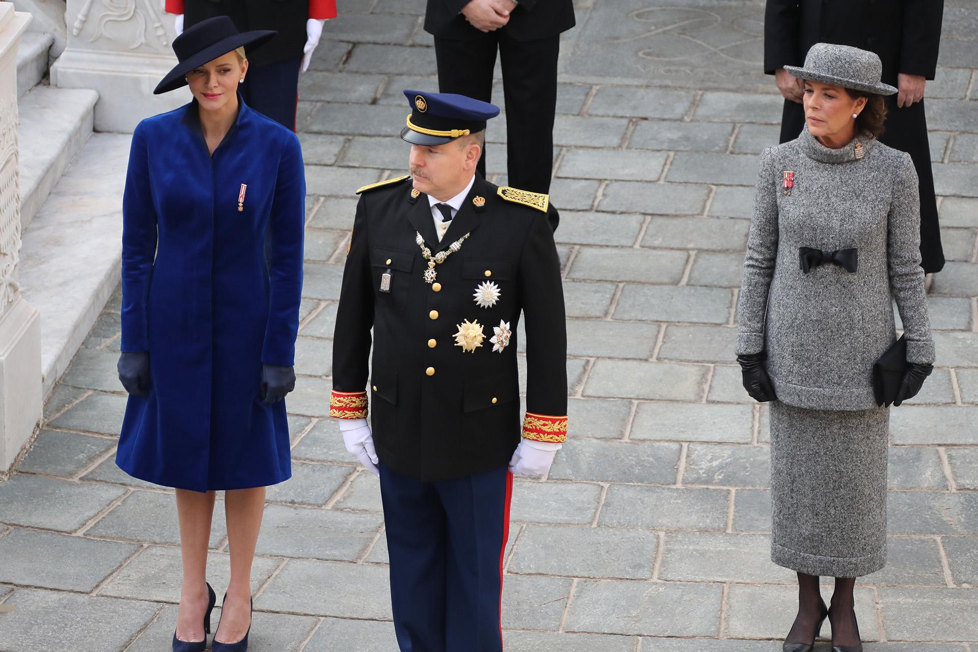 Duelo de estilos: mientras Charlene eligió un tapado de terciopelo azul con una gran pamela, Carolina se decantó por un conjunto gris claro