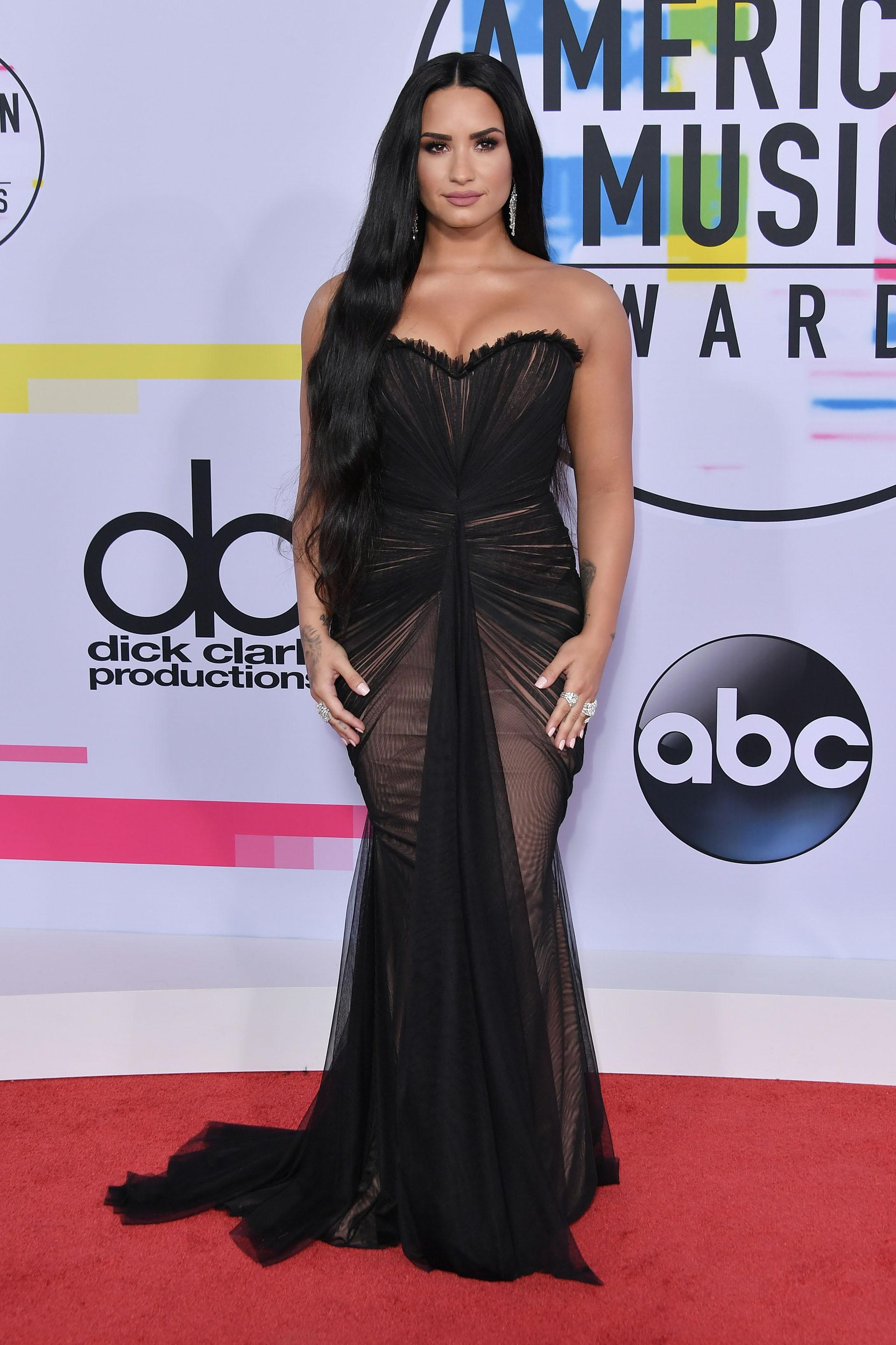Demi Lovato con un escote de alto impacto, transparencias y falda con cola
