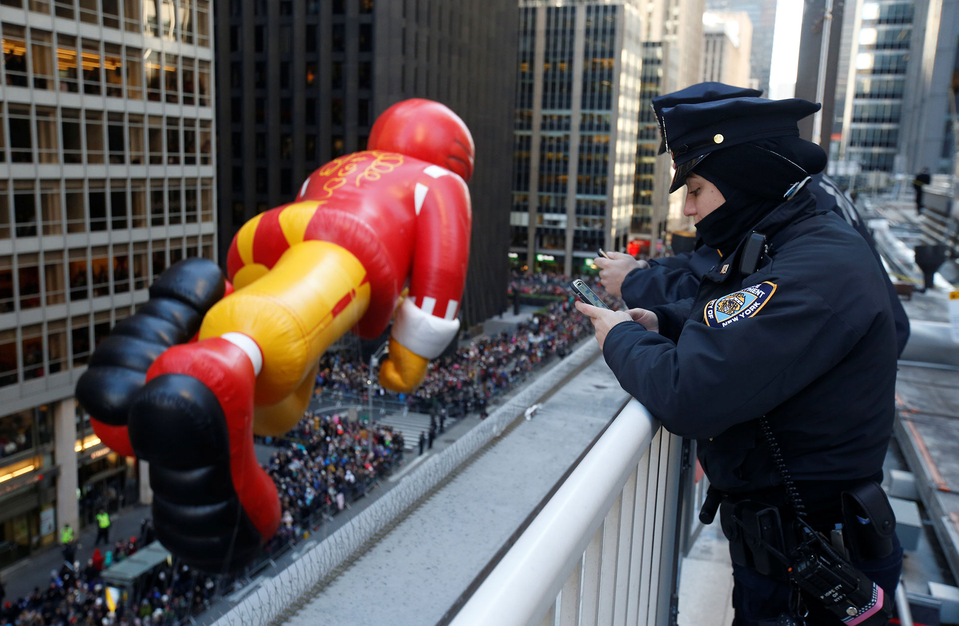 Los oficiales del Departamento de Policía de la Ciudad de Nueva York observan cómo el globo de Ronald McDonald desciende por la Sexta Avenida durante el Desfile del Día de Acción de Gracias de Macy's en el distrito de Manhattan de la ciudad de Nueva York, The York, Estados Unidos, el 23 de noviembre de 2017. (Reuters)