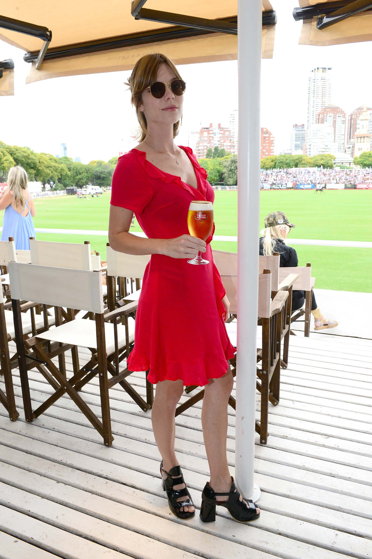 La actriz Laura Laprida disfrutó del evento con un vestido con detalles en volado en tono rojo y sandalias altas charol