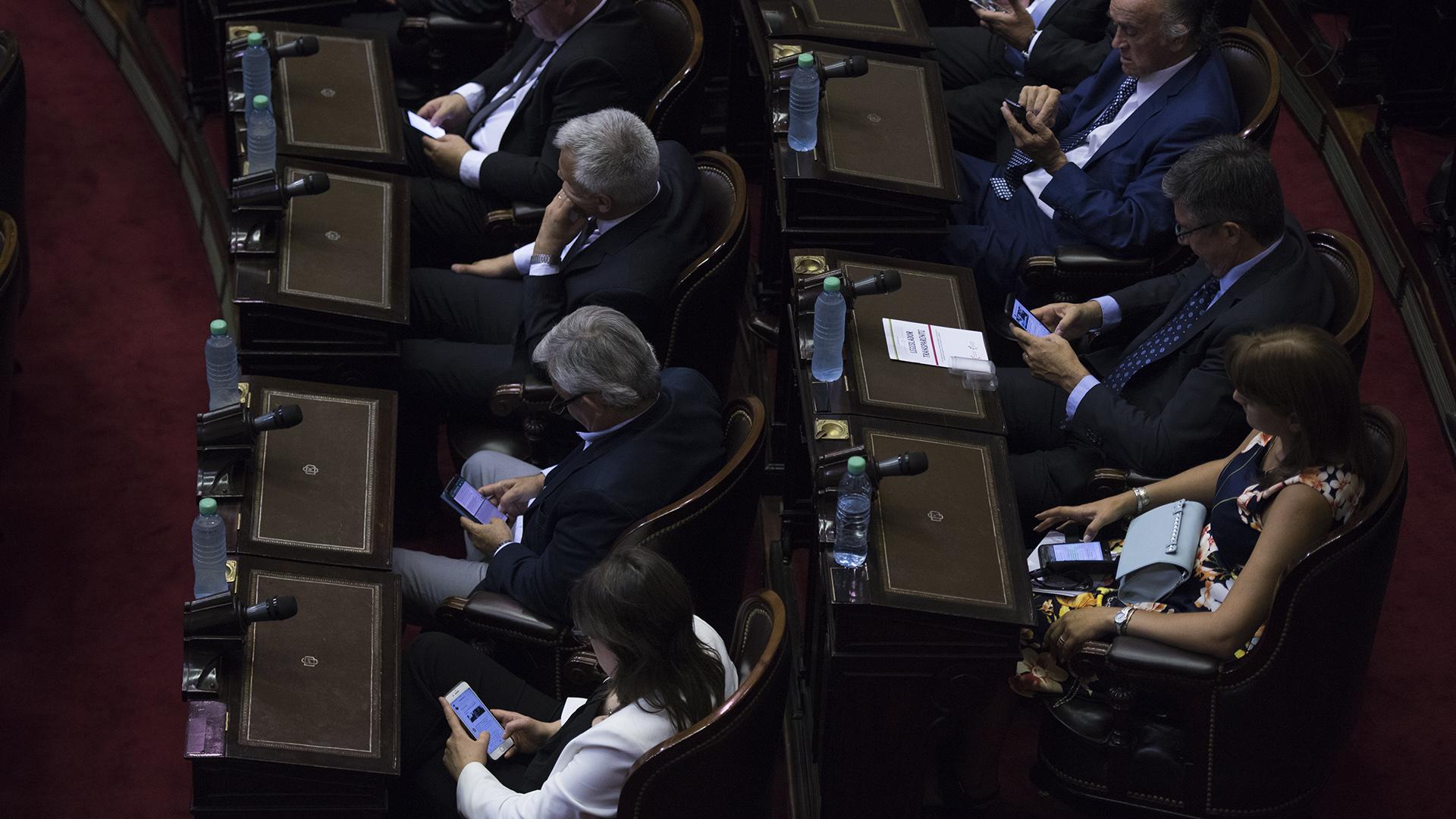 Legisladores miran su celular durante la sesión