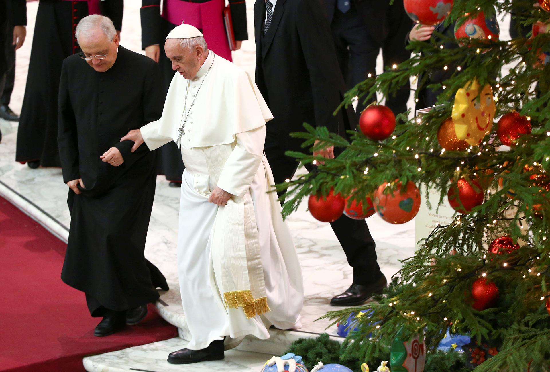 El papa Francisco camina asistido al pasar cerca al árbol del Vaticano, en la plaza San Pedro
