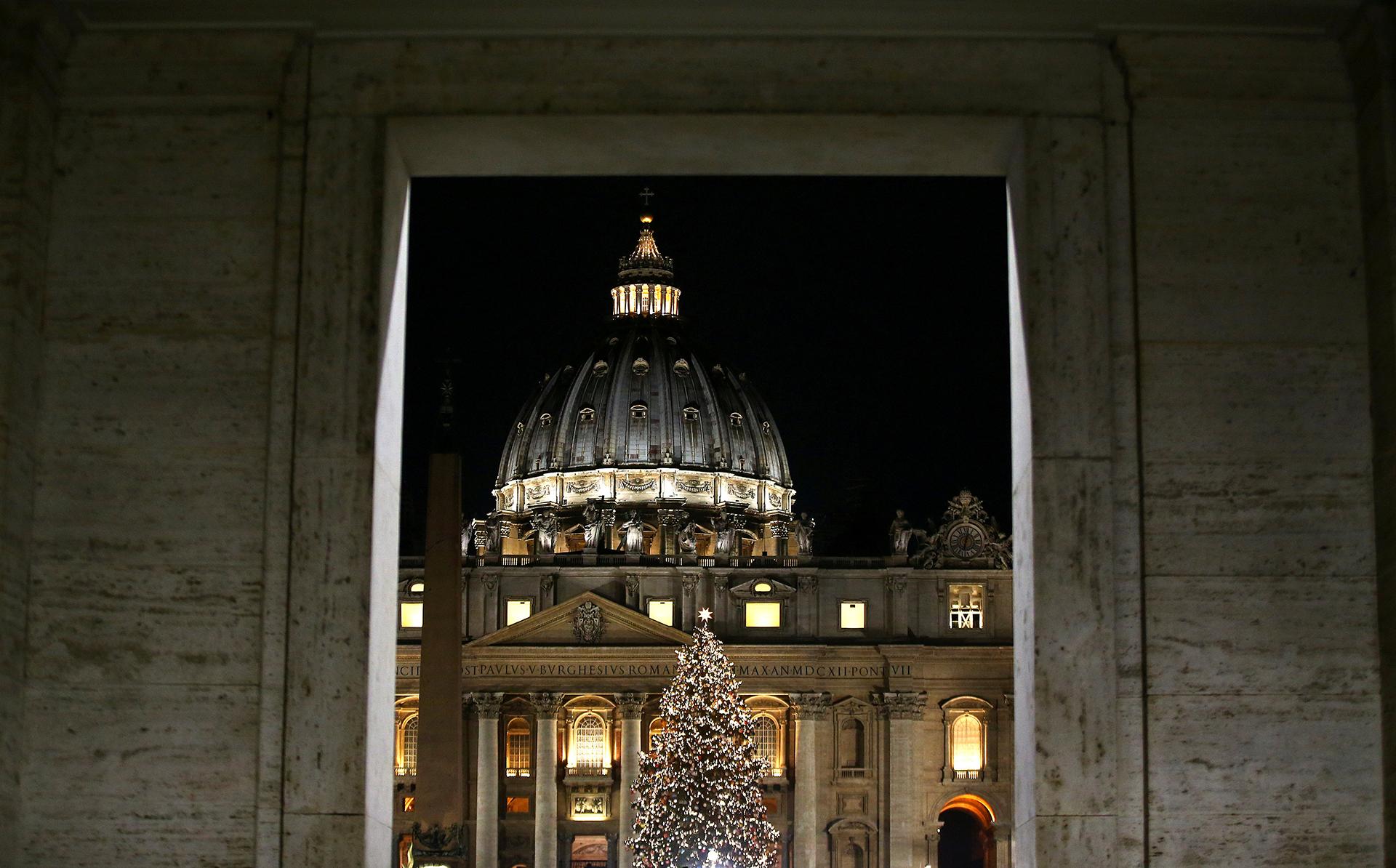 Una imagen del árbol del Vaticano iluminado con la tradicional cúpula detrás