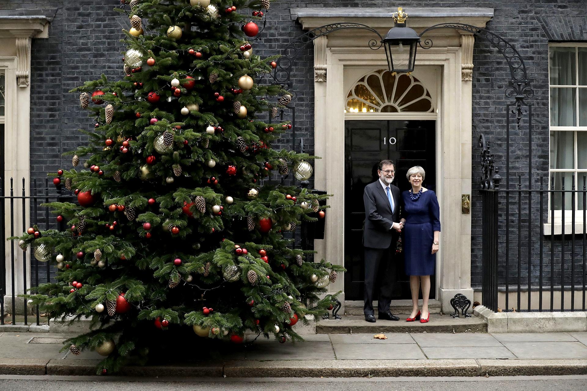 La primera ministra británica Theresa May y el presidente español Mariano Rajoy posan junto al árbol en la puerta de la sede del gobierno del Reino Unido, en el 10 deDowning Street, Londres