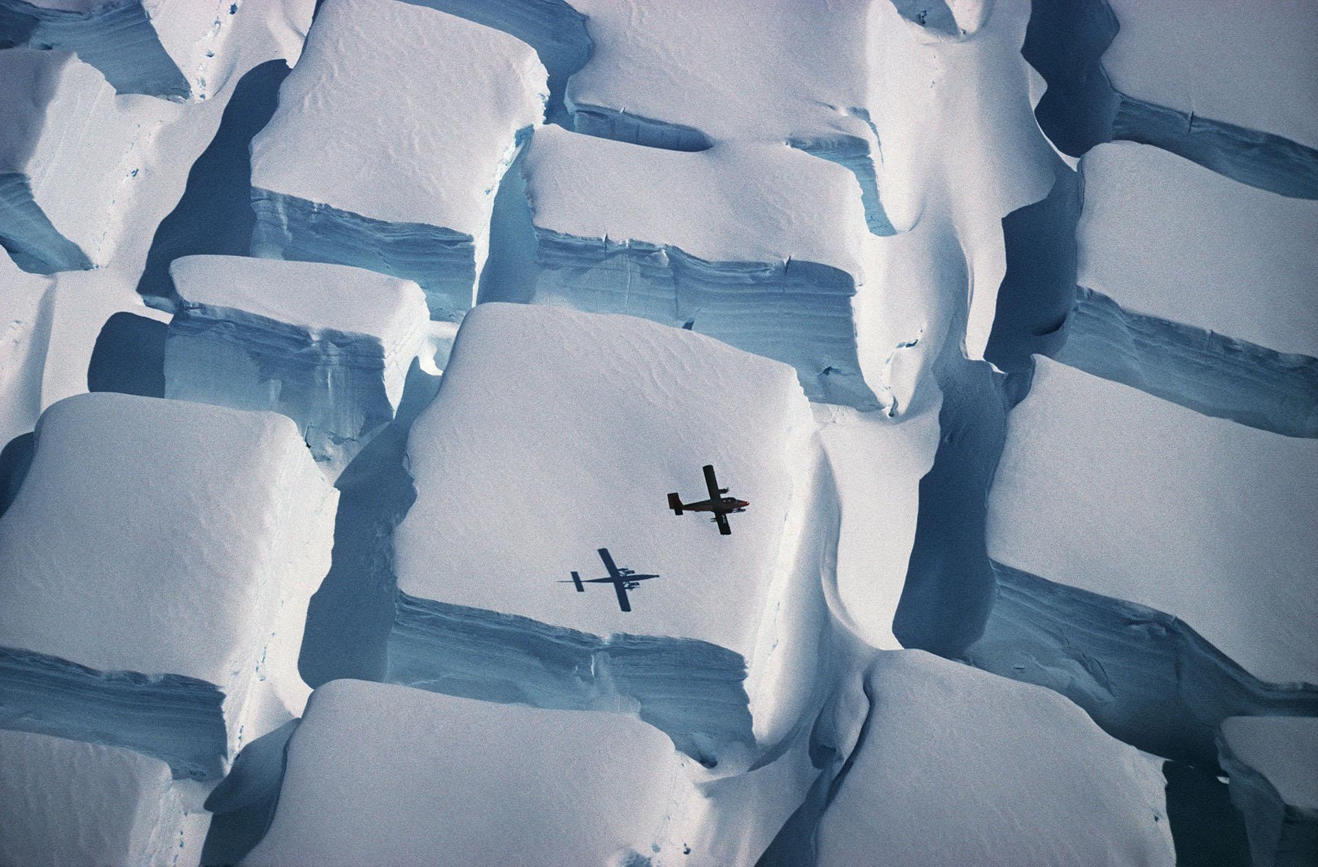 """Ganadora general y en categoría Ciencias de la Tierra y climatología. """"Cubitos de azúcar helados"""", por Peter Convey. La escala de la Antártida es impresionante pero difícil de entender. Esta foto, tomada a principios de 1995 durante un vuelo sobre la costa inglesa (península Antártica austral) a unos 74 grados al sur, ilustra la escala de grietas bidireccionales inusuales cuando una capa de hielo se estira en dos direcciones sobre una elevación subyacente, con un Avión Twin Otter para la escala. La foto fue tomada con una cámara Pentax ME Super y con un zoom de 70-300 mm en una película de diapositivas Kodachrome 64, sin detalles técnicos registrados, y ha sido escaneada en el British Antarctic Survey"""