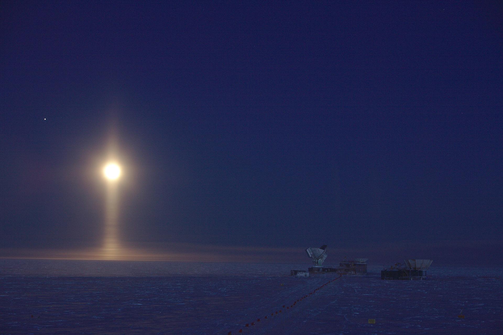 """Ganadora de la categoría Astronomía. """"Proyector lunar, Polo Sur, Antártida"""", por Daniel Michalik. Los cristales de hielo suspendidos en la atmósfera crean un raro fenómeno óptico: un pilar de luz debajo de la Luna. Tres de los telescopios ubicados en el polo sur son visibles a la derecha de la imagen. Una línea de banderas ayuda a encontrar el camino a los telescopios durante los cinco meses de oscuridad continua. Júpiter es visible como un punto brillante a la izquierda de la Luna. El fotógrafo actualmente está invernando en el Polo Sur y trabajando para el Telescopio del Polo Sur de 10 m, el plato de radio más a la izquierda visible en la imagen. La imagen se tomó como una sola exposición larga a -60 ° C con ajustes menores de contraste y exposición"""