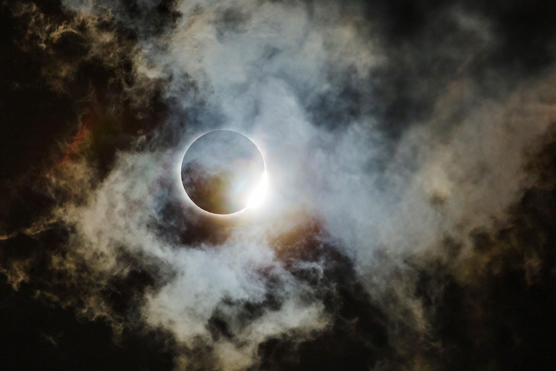 """Finalista en categoría Astronomía. """"Anillo de diamante a través de nubes delgadas"""", por Wei-Feng Xue. El eclipse estadounidense de 2017 visto desde la ruta que atraviesa el norte de Georgia. Este es el anillo de diamantes que ilumina algunas estructuras de nubes muy finas, casi como nubes espaciales (es decir, una nebulosa). También en la foto, la corona solar se atenuó un poco por las nubes finas, pero aún era visible. Esta foto fue tomada con una cámara réflex digital Canon EOS 6D con un extensor Canon EF 70-200mm + 2x a 400 mm, y se procesó con Photoshop CC"""