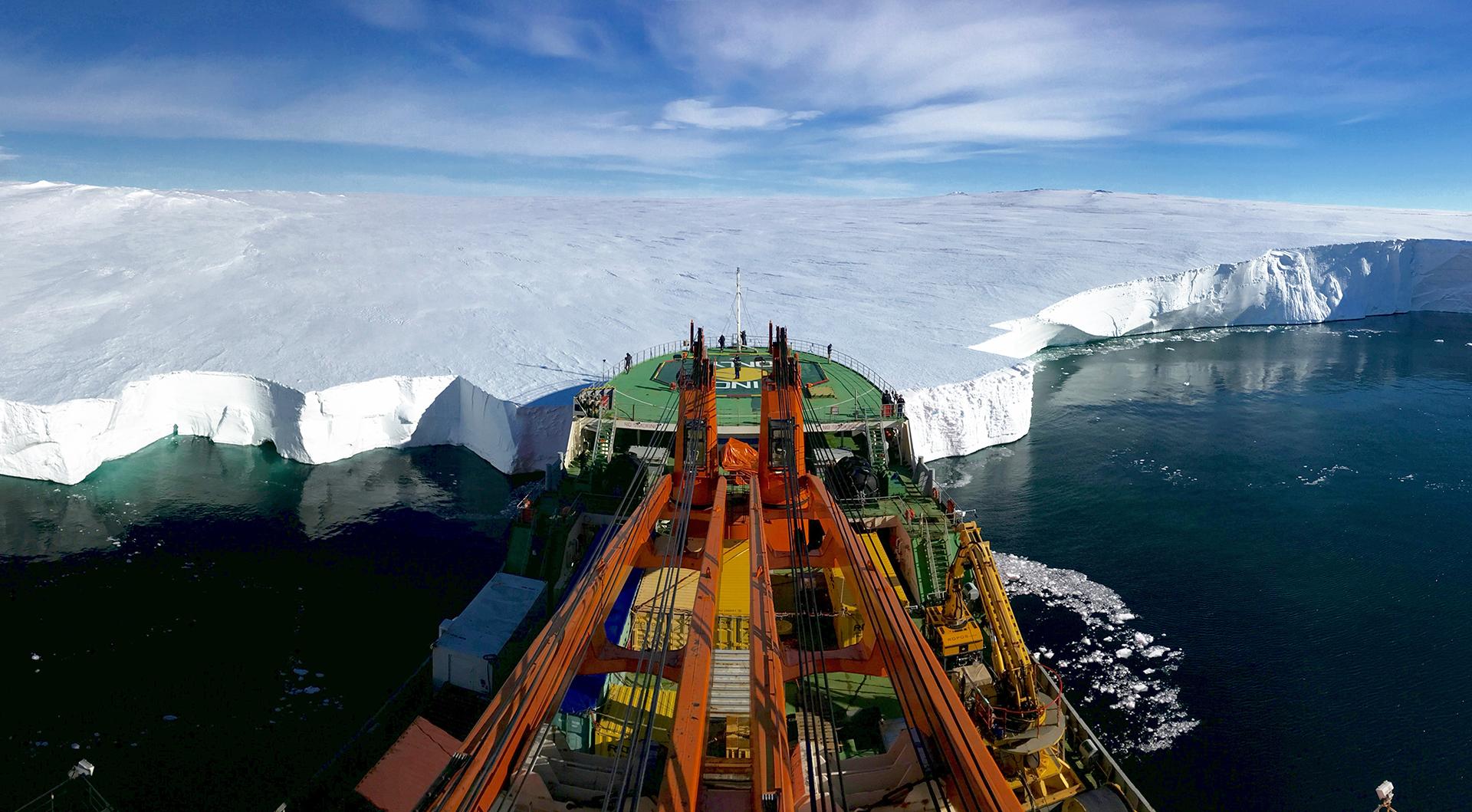 """Finalista en Ciencias de la Tierra y climatología. """"Inclinese primero"""", por Giuseppe Suaria. El buque de investigación ruso Akademik Tryoshnikov apoya la proa contra el morro del glaciar Mertz en la Antártida oriental. La foto fue tomada momentos antes de desplegar ROPOS, un Vehículo Submarino Operado Remoto (ROV) bajo la lengua del glaciar para investigar el derretimiento de la capa de hielo después de que un trozo de hielo que sobresalía 100 kilómetros (62 millas) hacia el Océano Austral se separó del cuerpo principal de la lengua en 2010"""