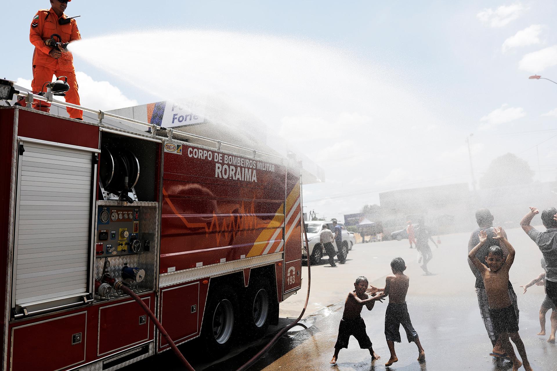 Bomberos brasileños mojan a niños venezolanos en Boa Vista, estado de Roraima (REUTERS)
