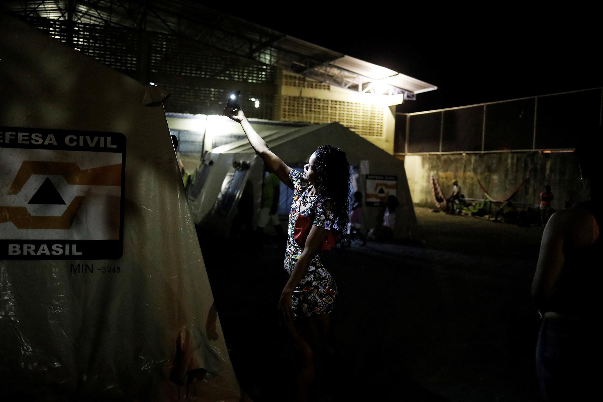 Una mujer prende una lamparita en los refugios (REUTERS)