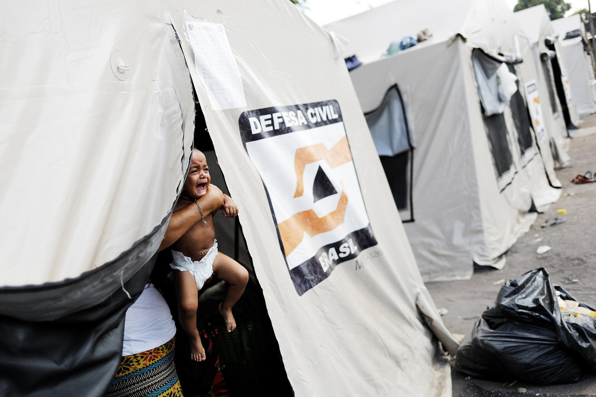 Un bebé llora en una de las carpas de refugiados venezolanos (REUTERS)