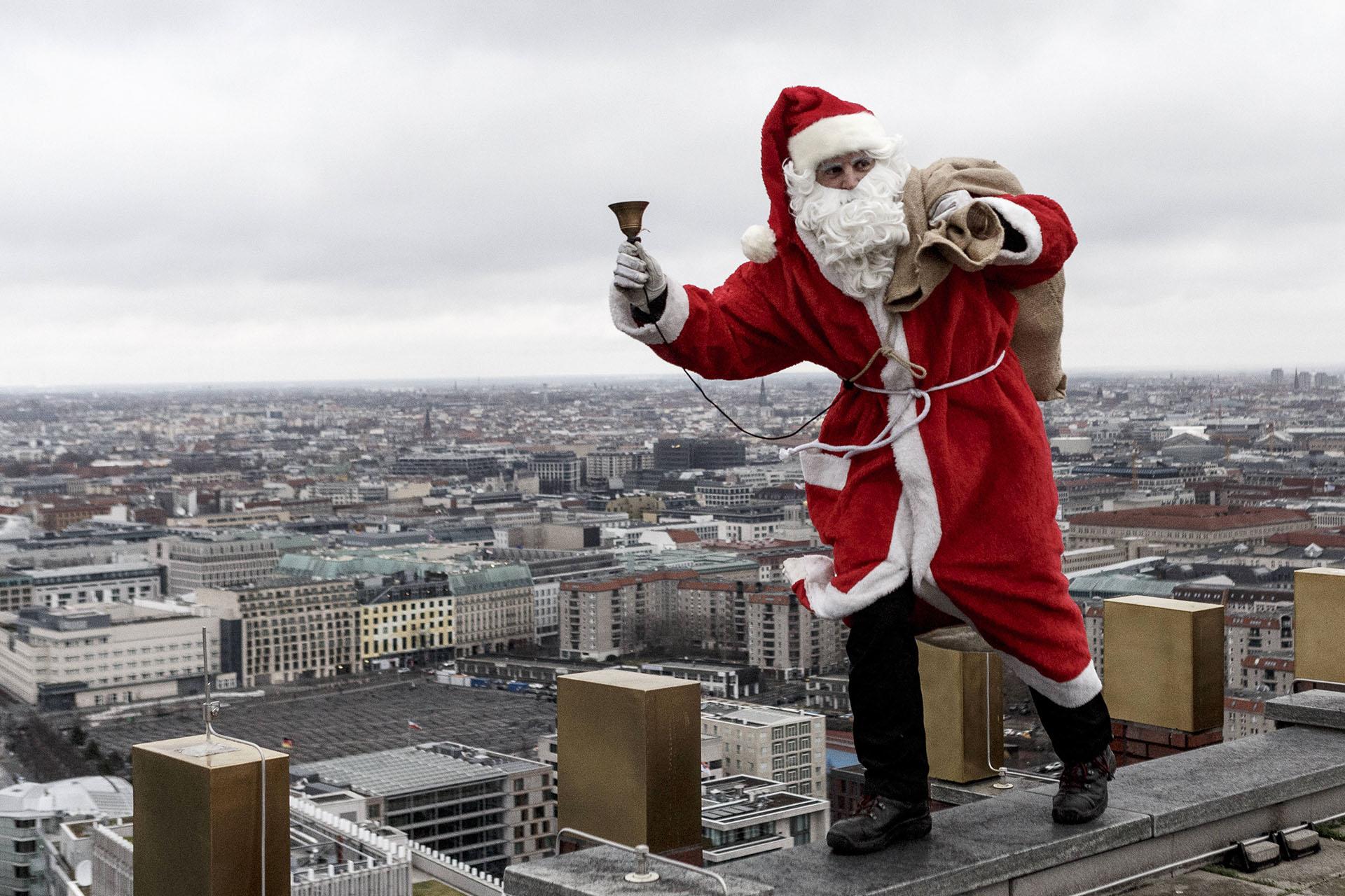 Un actor vestido como Papá Noel pretende recuperar un paquete perdido cerca de la torre Kollhoff el 17 de diciembre de 2017 en Berlín, Alemania. (Getty Images)