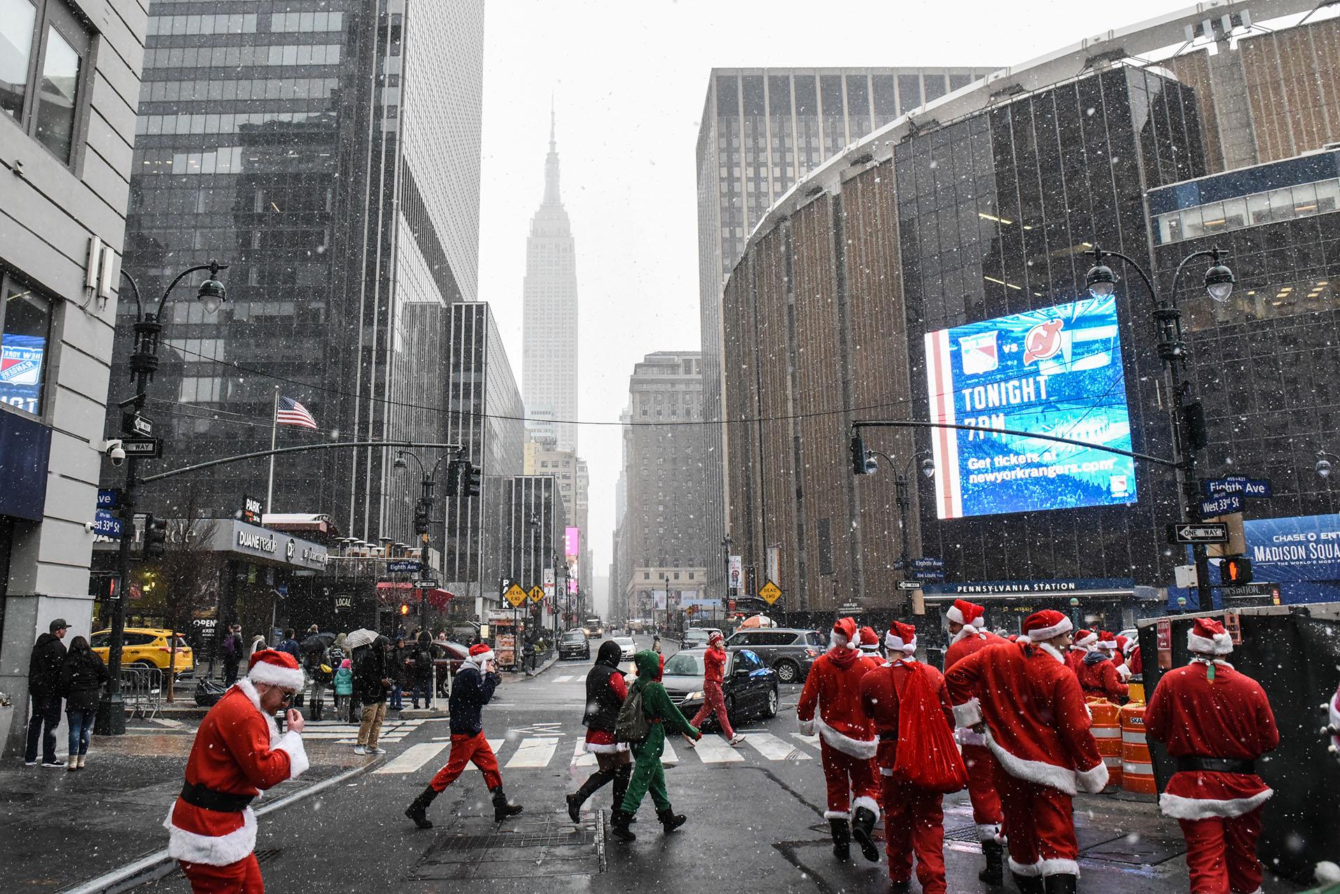 Personas vestidas como Santa Claus participan en el bar hopping anual SantaCon el 9 de diciembre de 2017 en la ciudad de Nueva York. (Getty Images)