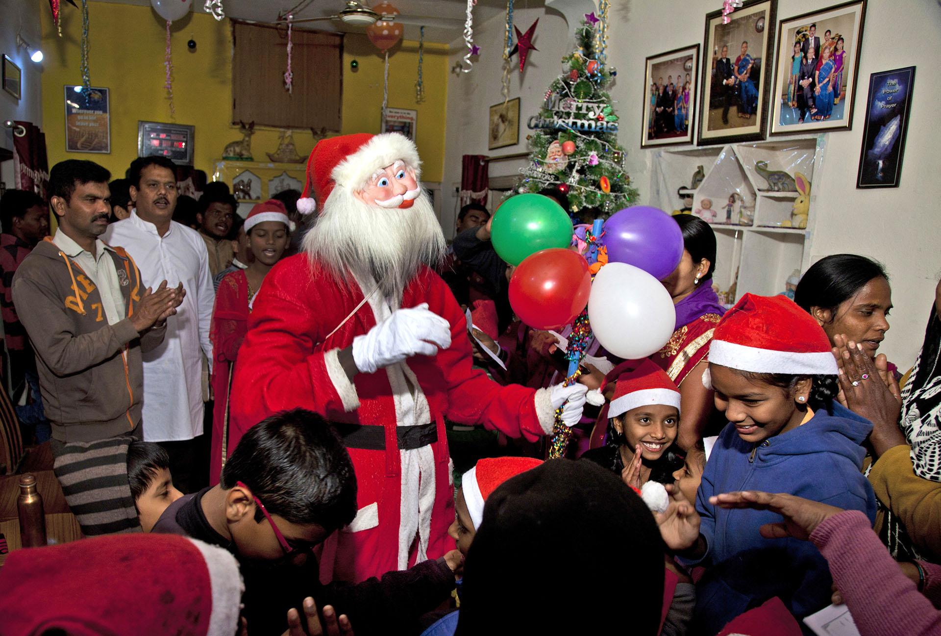 un indio vestido de Santa Claus canta villancicos navideños con niños en Hyderabad, India, el 19 de diciembre de 2017. (AP)