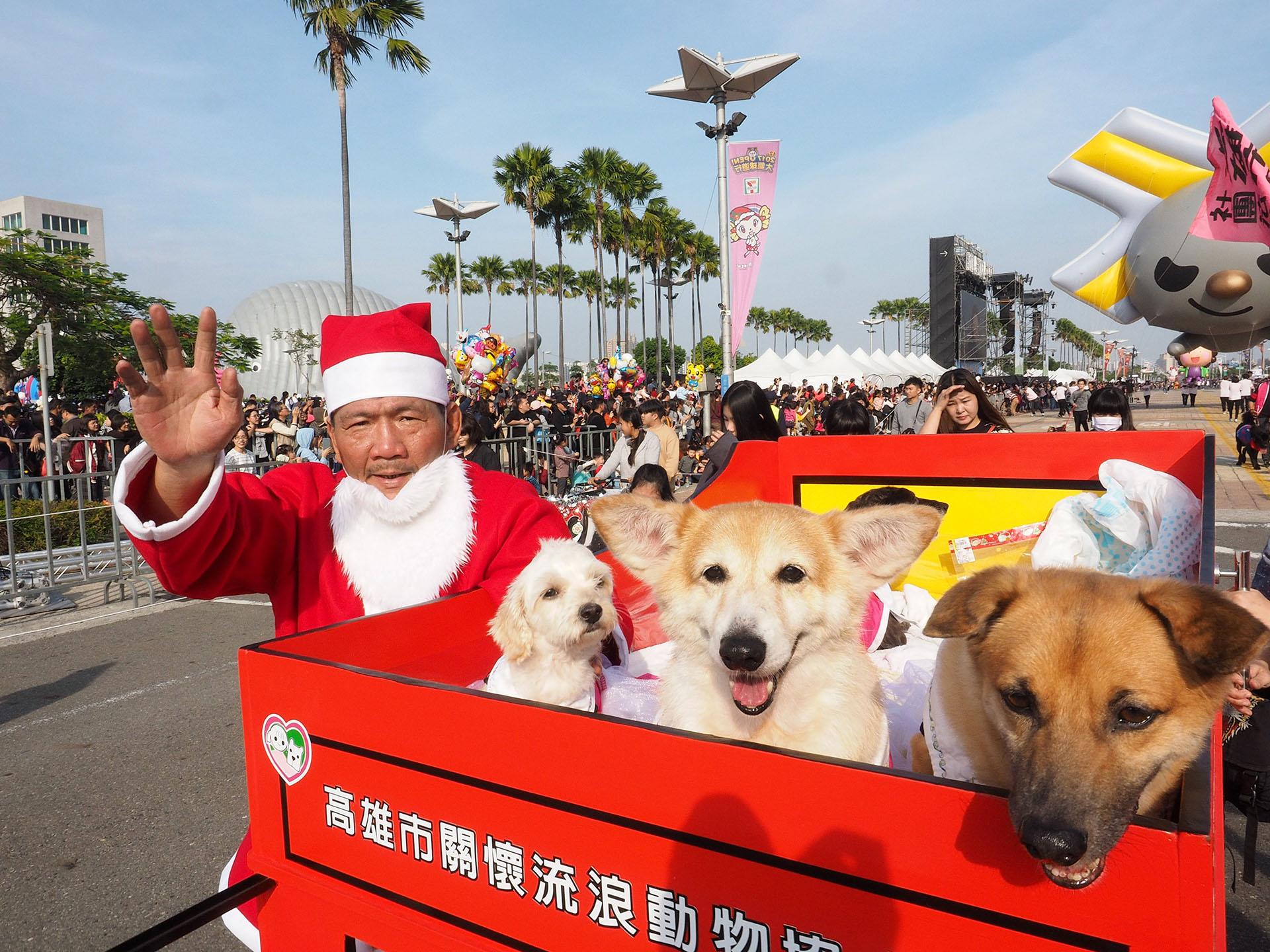 Un hombre vestido de Papá Noel posa para fotografías con perros durante el Desfile de Globos en Kaohsiung, al sur de Taiwán, el 16 de diciembre de 2017. (EFE)