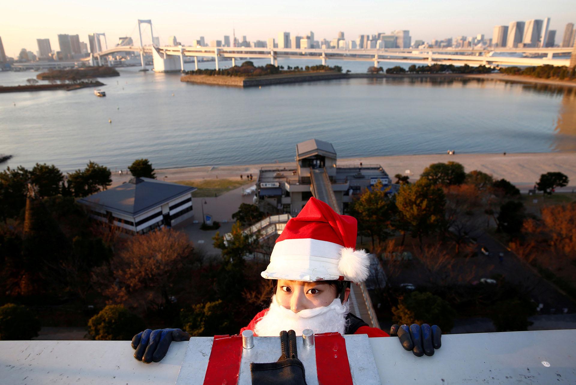 Una limpiadora de ventanas femenina vestida como Santa Claus se prepara para limpiar una ventana de vidrio en un evento para celebrar la próxima Navidad en DECKS Tokyo Beach en Tokio, Japón, el 21 de diciembre de 2017. (Reuters)