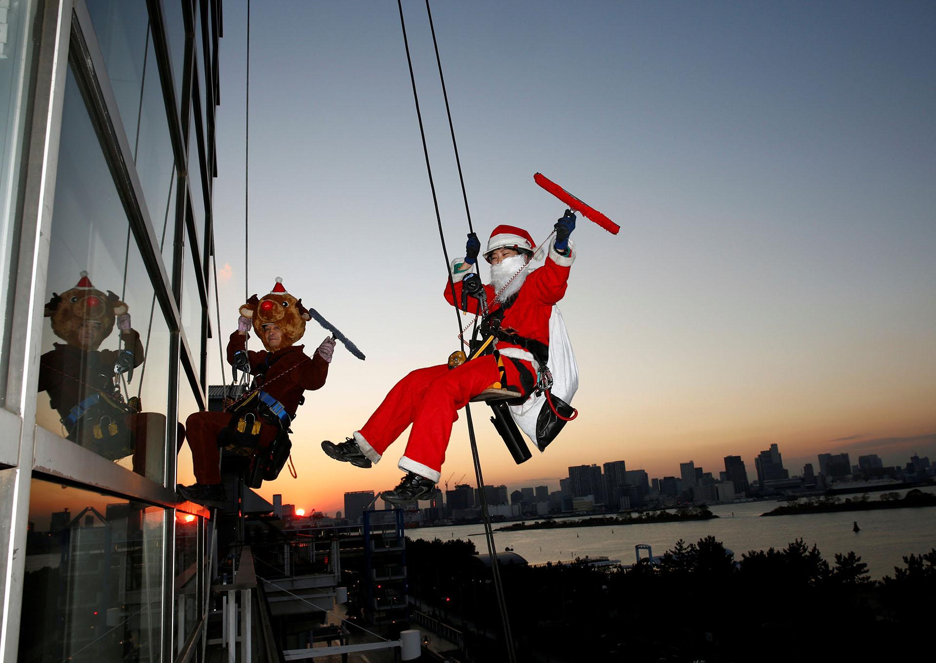 Los limpiadores de ventanas vestidos como Santa Claus y un reno posan para los fotógrafos mientras limpian una ventana de vidrio en un evento para celebrar la próxima Navidad en DECKS Tokyo Beach en Tokio, Japón, el 21 de diciembre de 2017. (Reuters)