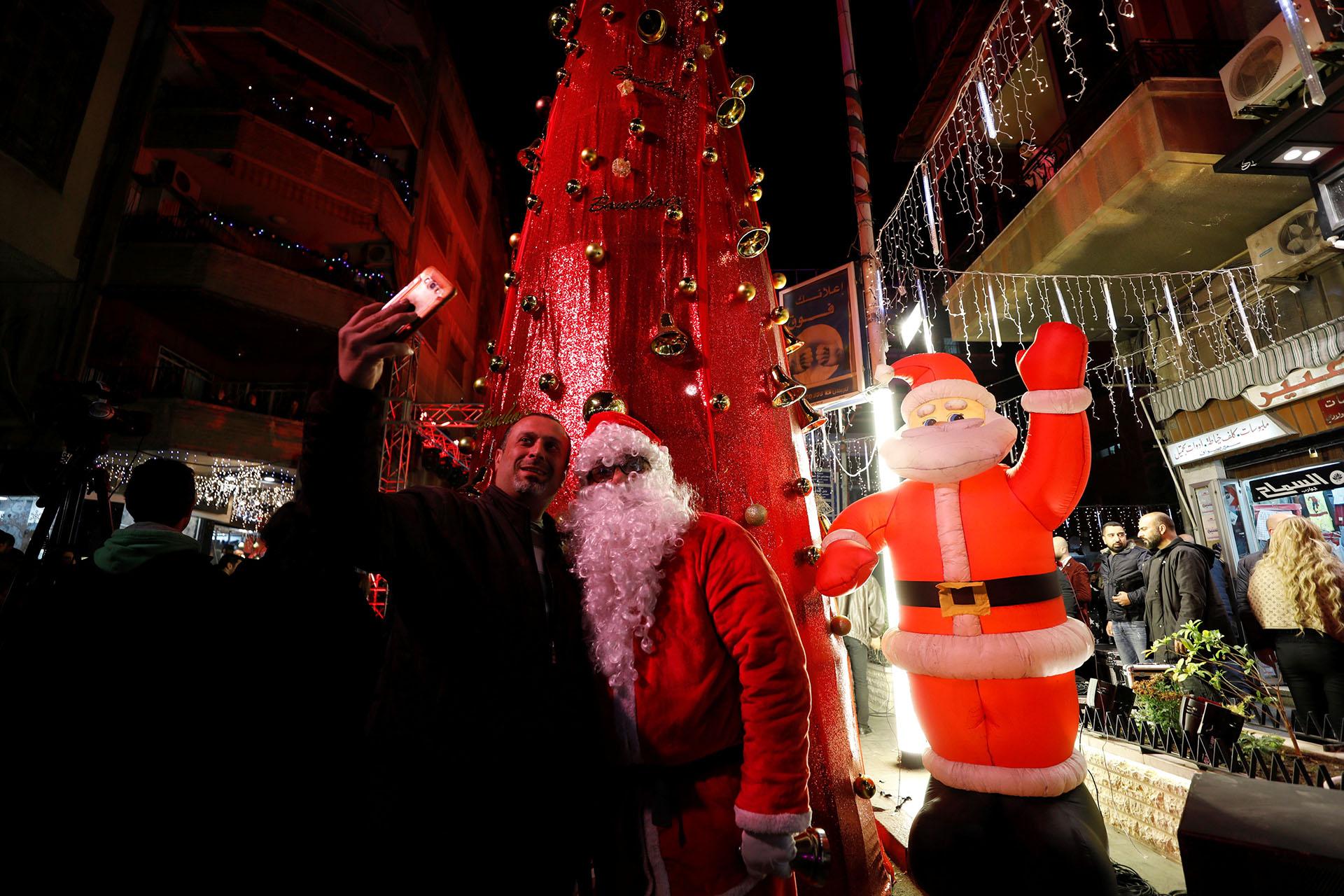 Un hombre se toma una selfie con un hombre vestido como Papá Noel durante un festival de Navidad en Damasco, Siria, el 20 de diciembre de 2017. (Reuters)
