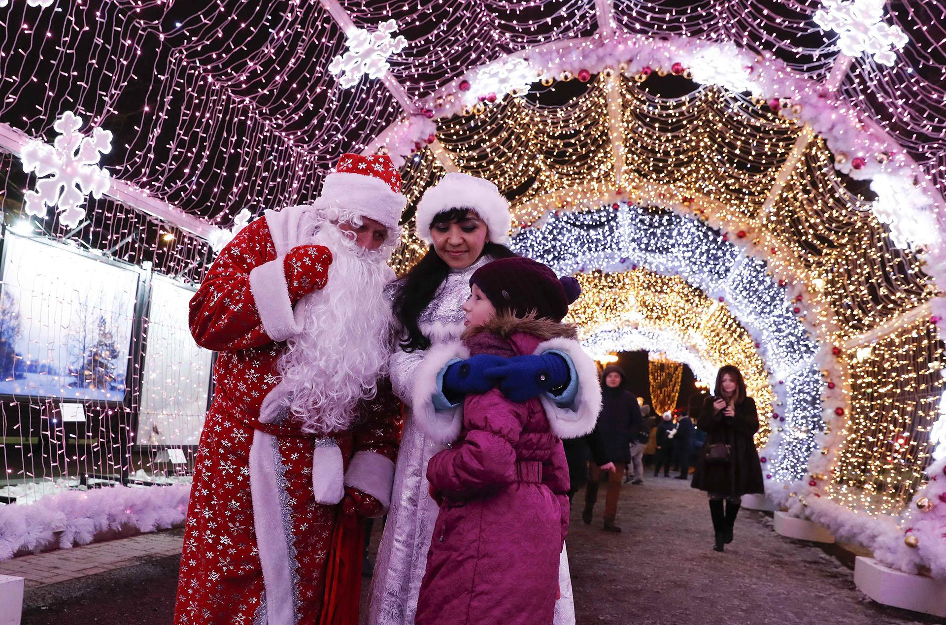 La gente vestida como el Padre Frost, el equivalente ruso de Santa Claus, y la Doncella de Nieve conversan con una chica mientras se encuentran bajo decoraciones festivas para el próximo Año Nuevo y la temporada navideña en el centro de Moscú, Rusia 20 de diciembre de 2017. (Reuters)