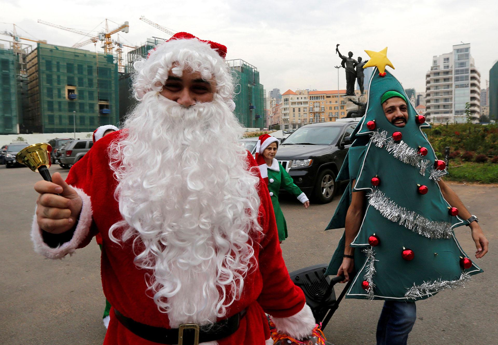 Gente vestida de elfos navideños alrededor de Santa Claus entregando donas en Beirut, Líbano el 20 de diciembre de 2017. (Reuters)